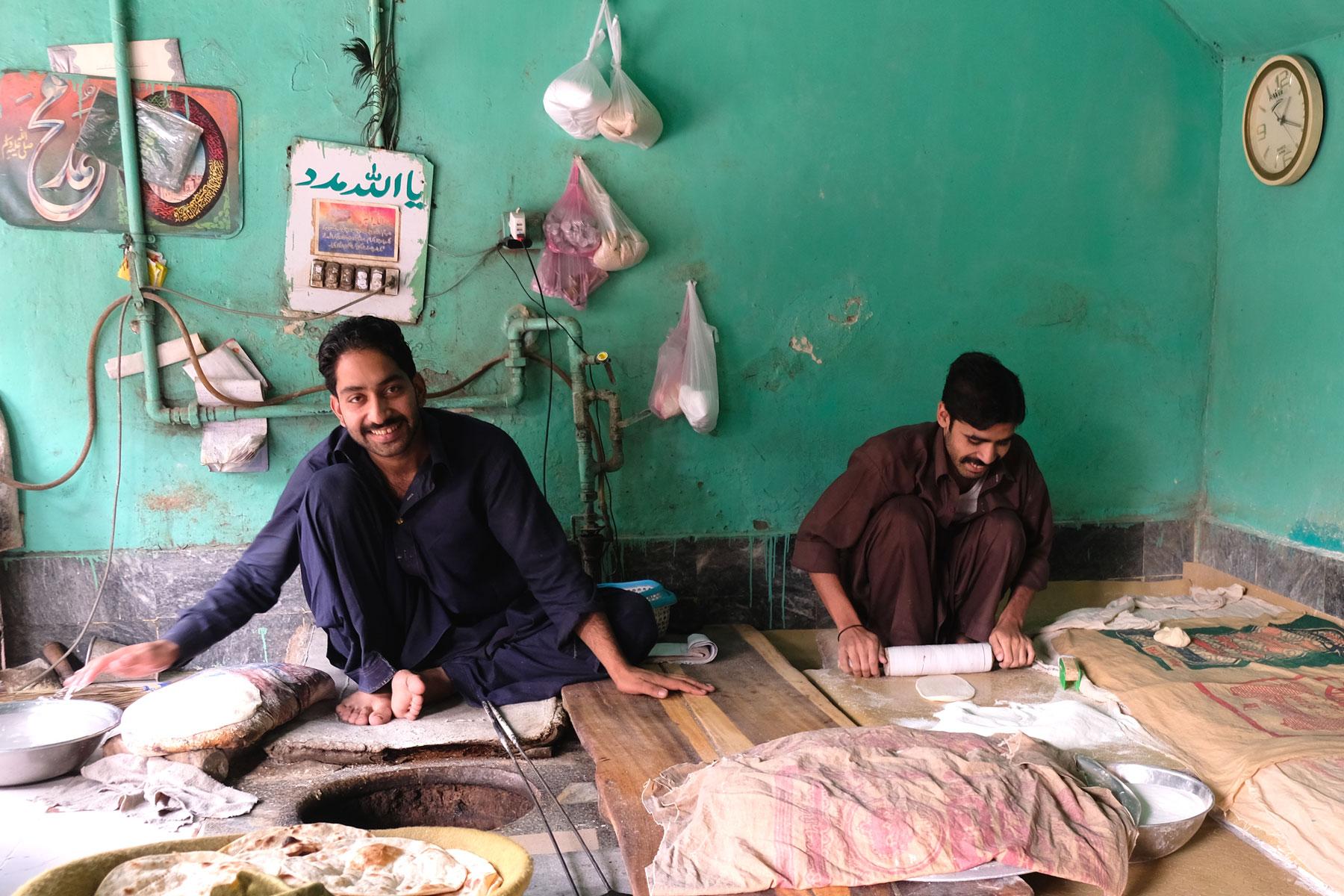 Pakistanische Männer rollen auf dem Boden hockend Teig für Fladenbrote aus.