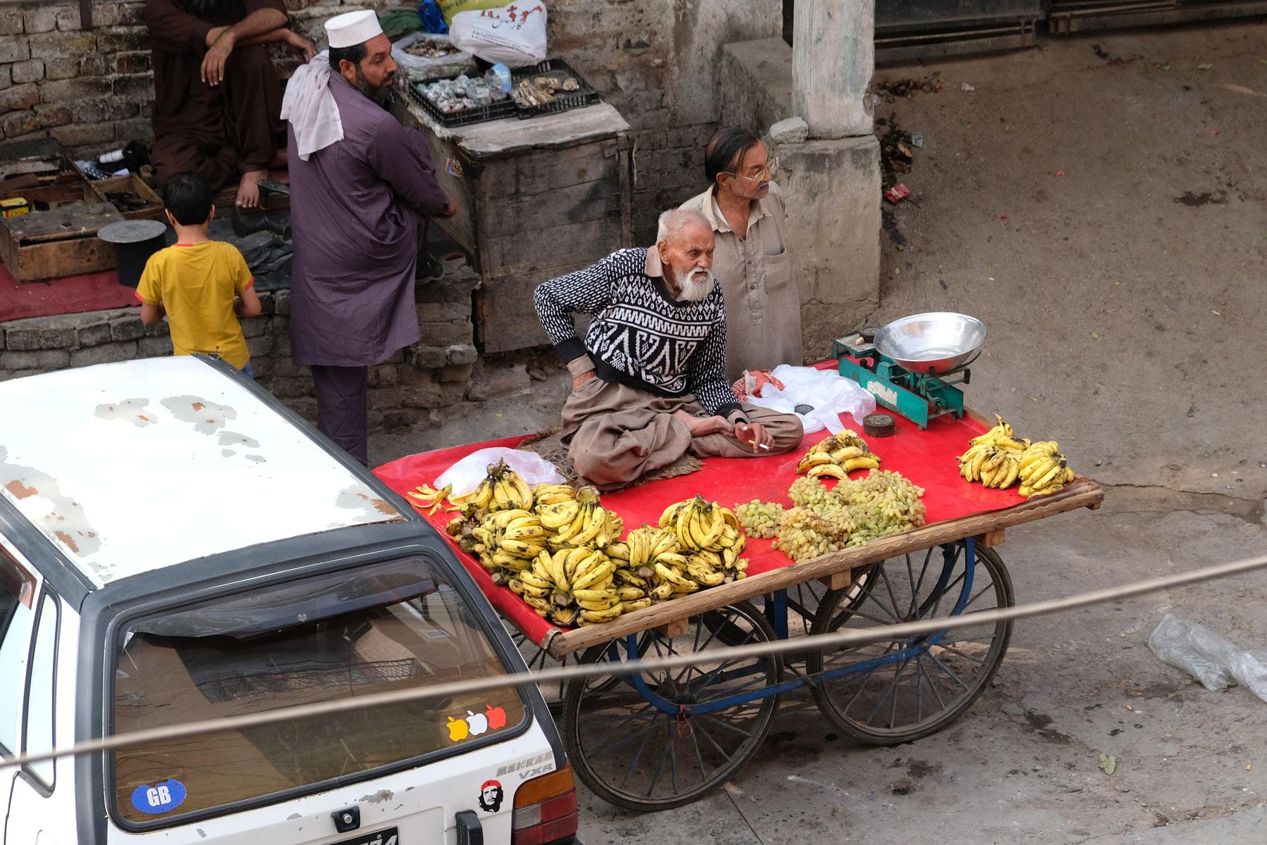 Ein alter Mann sitzt in Rawalpindi auf einem Wagen, auf dem Bananen und Trauben verkauft werden.