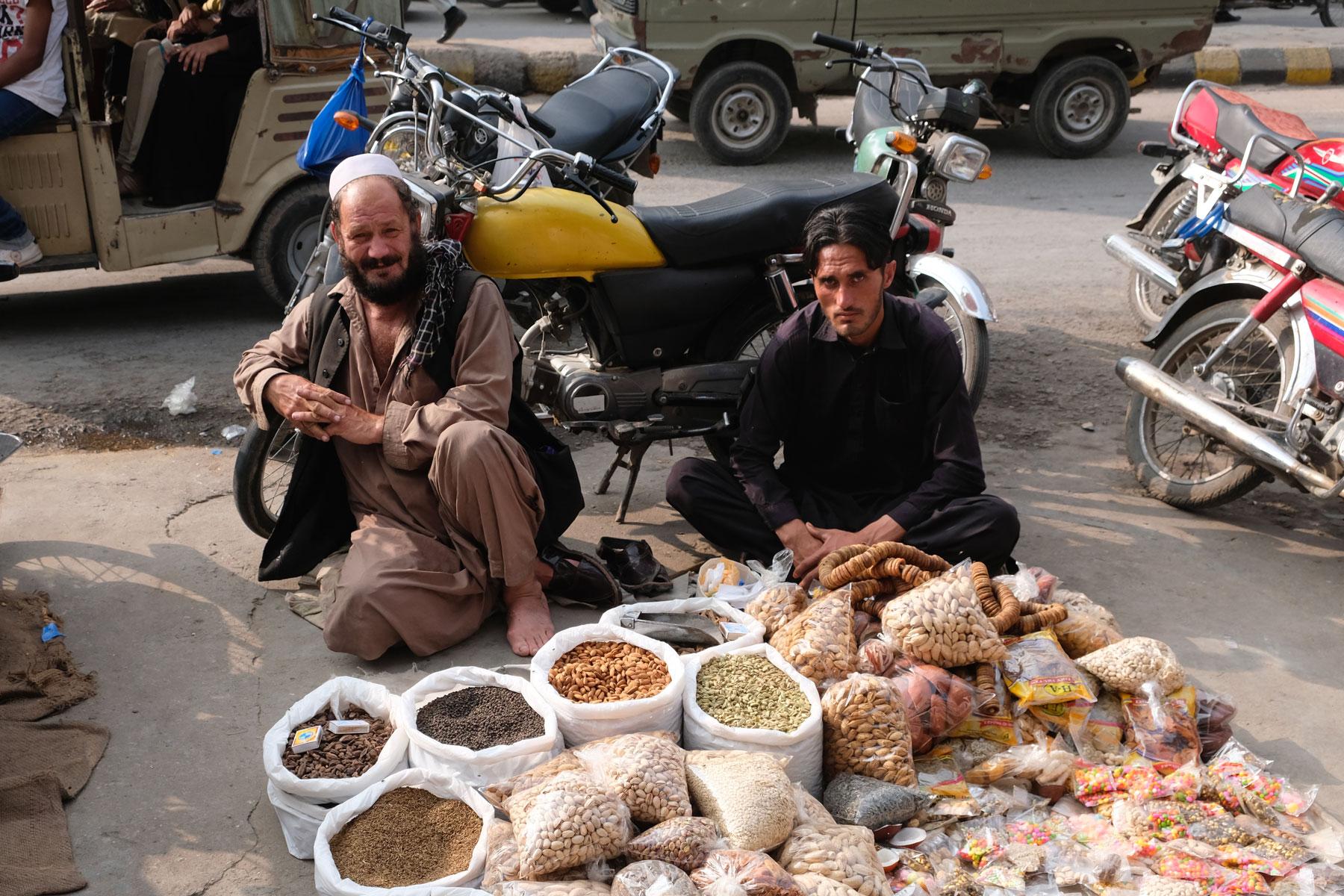 Zwei Männer sitzen auf dem Boden und verkaufen Trockenfrüchte und Nüsse.