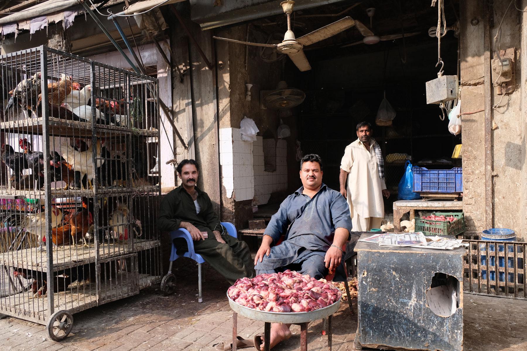 Männer sitzen an einem Straßenstand in Rawalpindi, an dem Hühnchenfleisch verkauft wird.