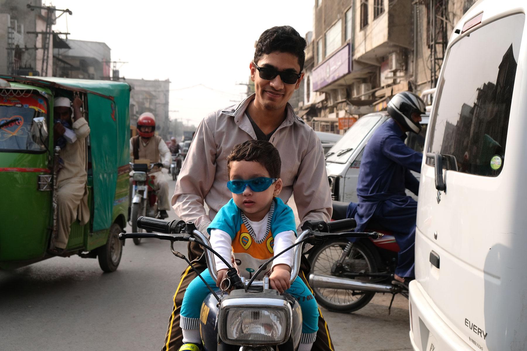 Ein Mann und ein verkleideter Junge sitzen auf einem Motorrad in Rawalpindi.
