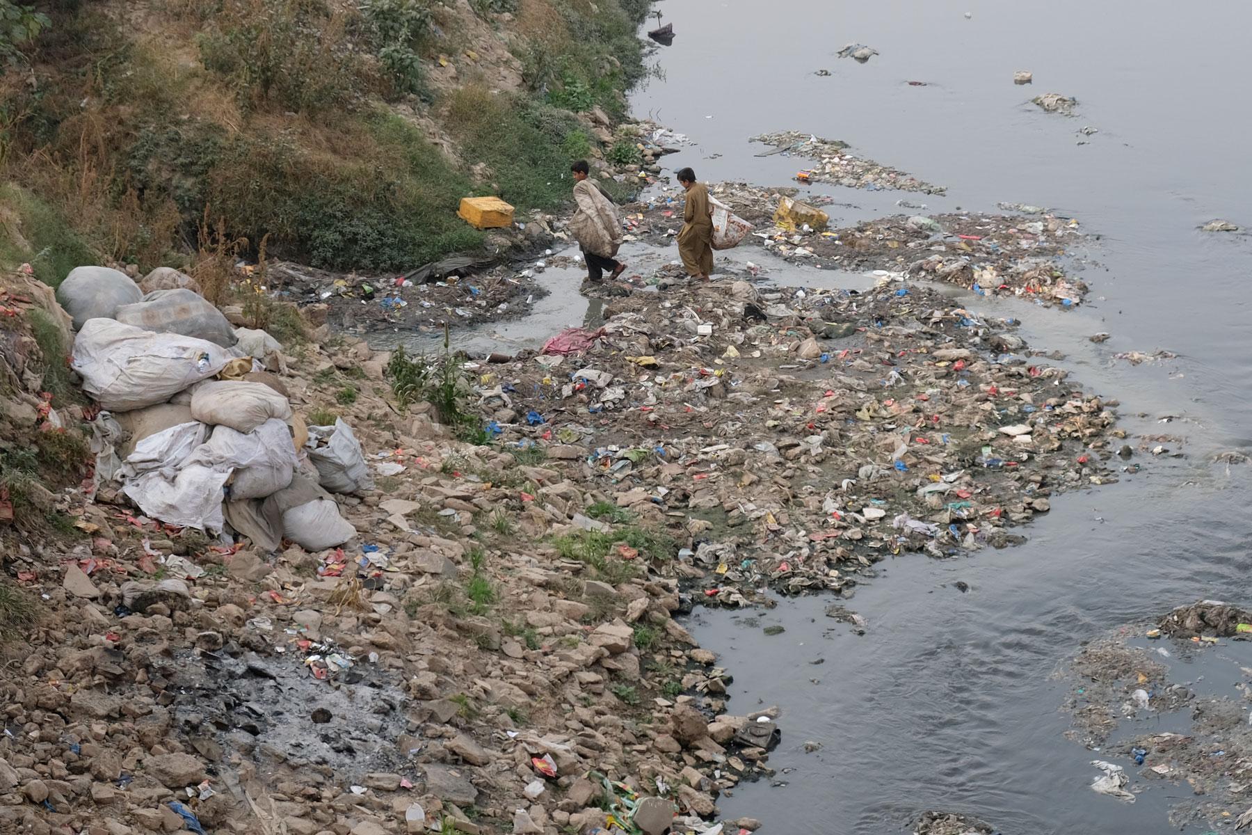 Zwei Jungen suchen am Ufer eines Flusses im Müll nach Brauchbarem.