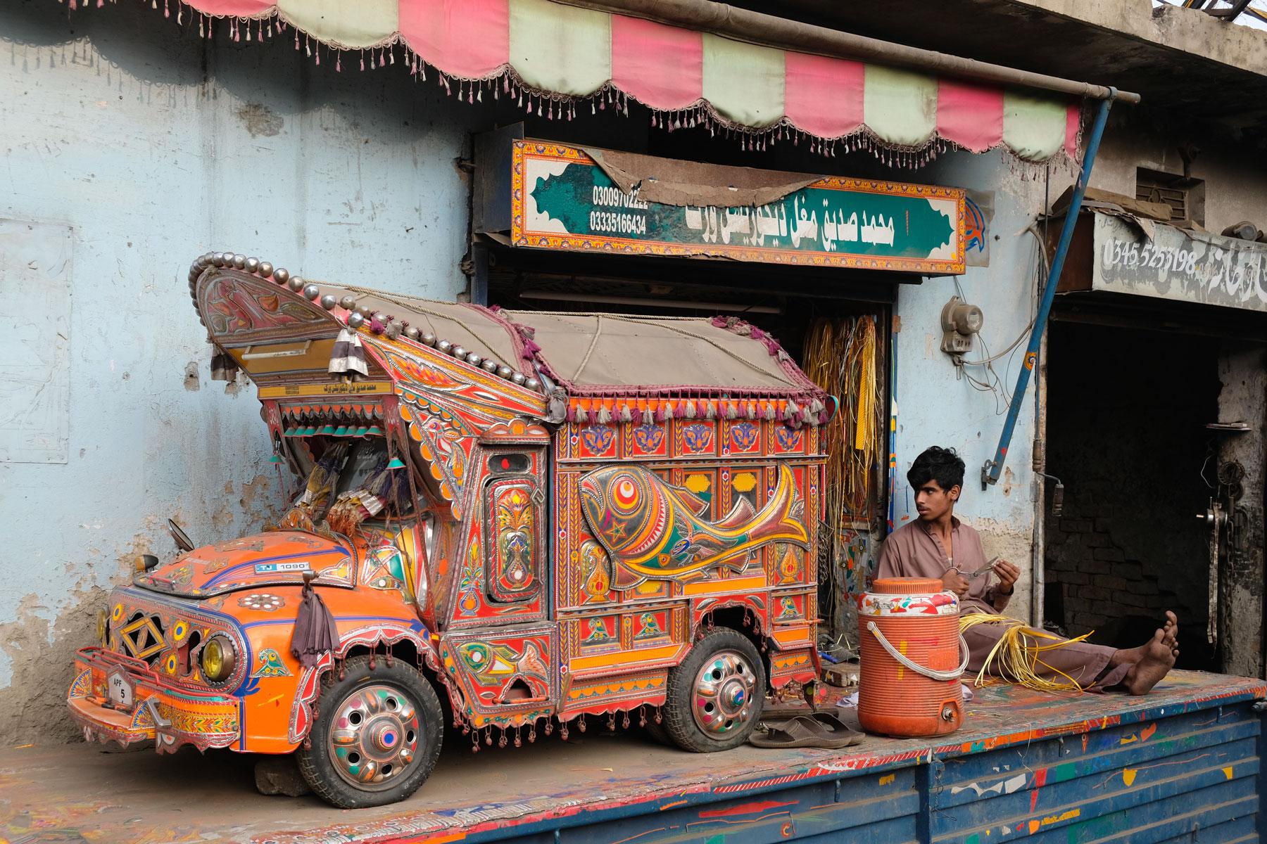 Ein Junge neben einem Miniaturmodell eines pakistanischen Lastwagens.