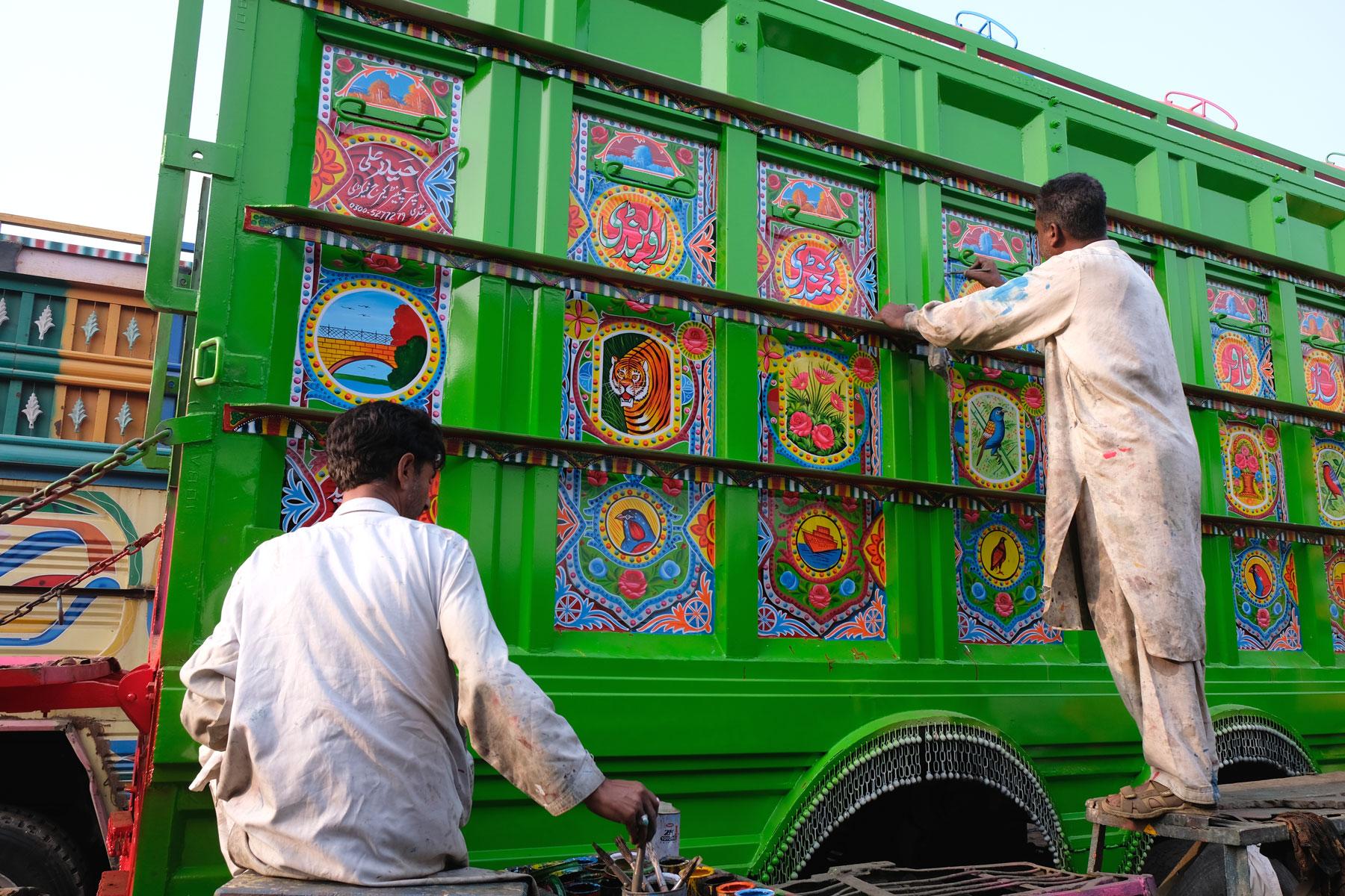 Zwei pakistanische Männer bemalen einen Lastwagen in Rawalpindi.