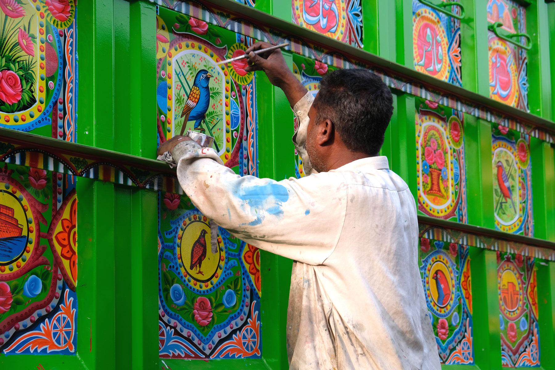 Ein Mann verschönert einen Lastwagen in Rawalpindi mit Truck Art.