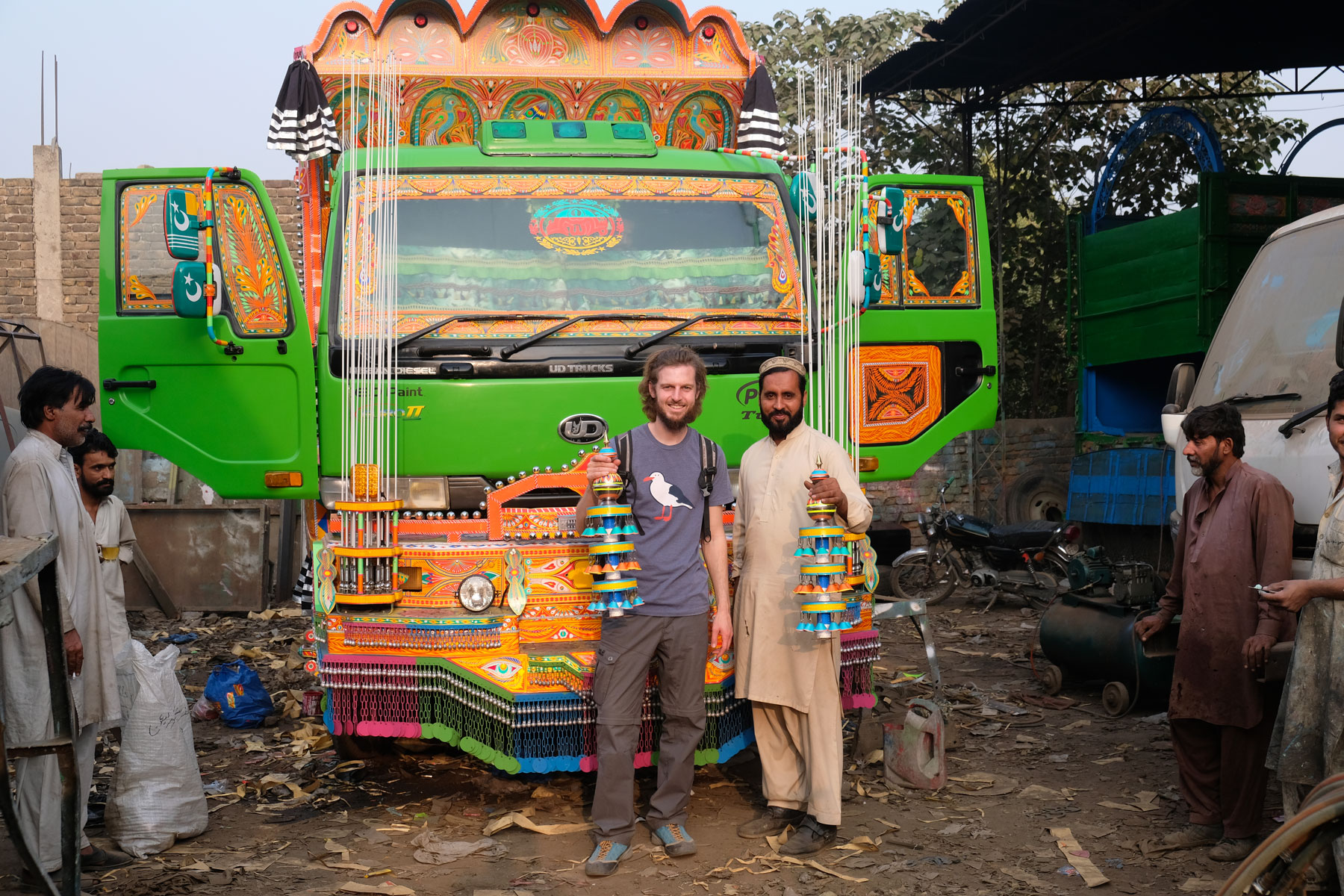 Sebastian steht neben einem Mann. Beide halten einen Gegenstand zur Verschönerung von Lastwagen in der Hand.