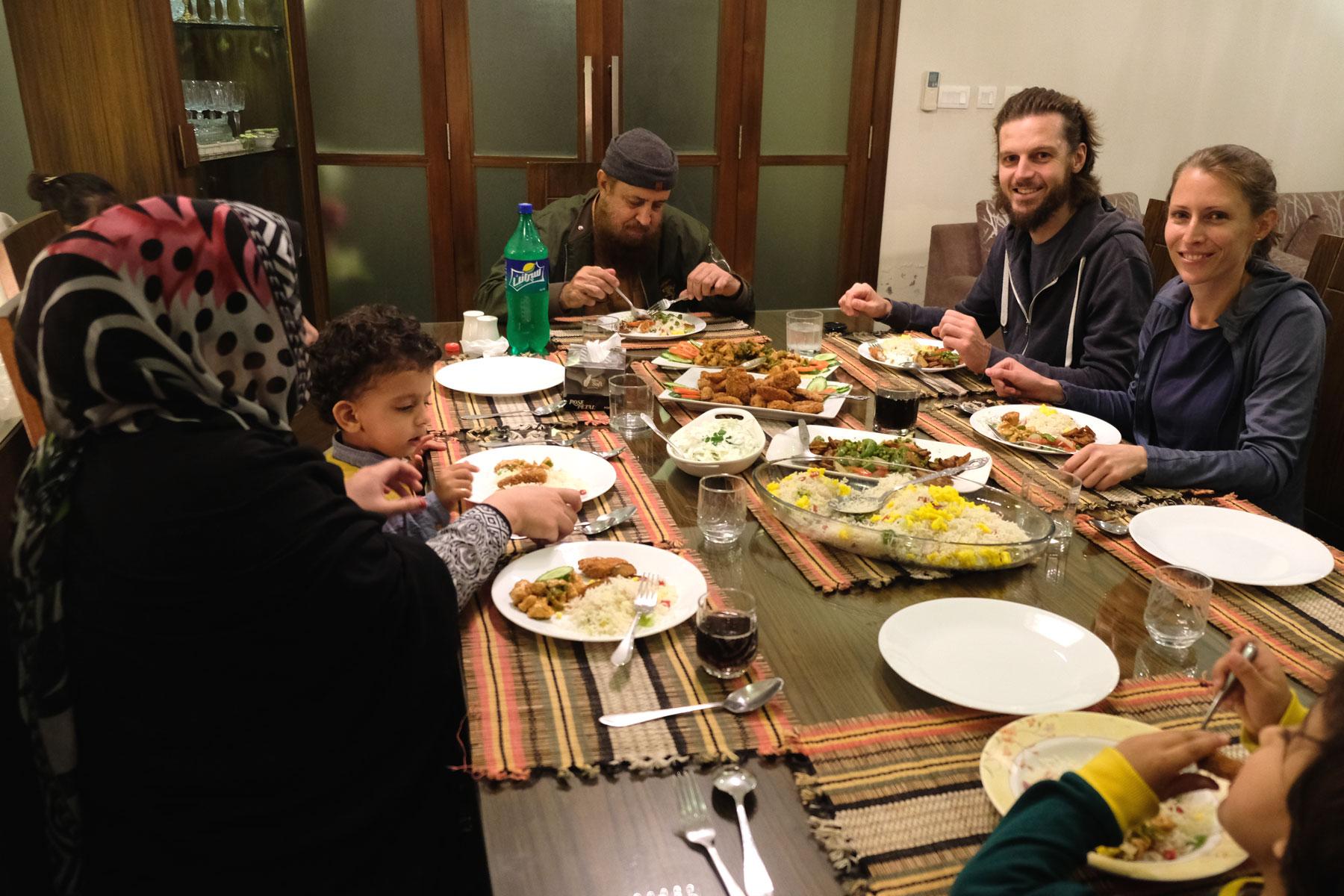 Sebastian und Leo sitzen mit einer pakistanischen Familie in Islamabad beim Abendessen.