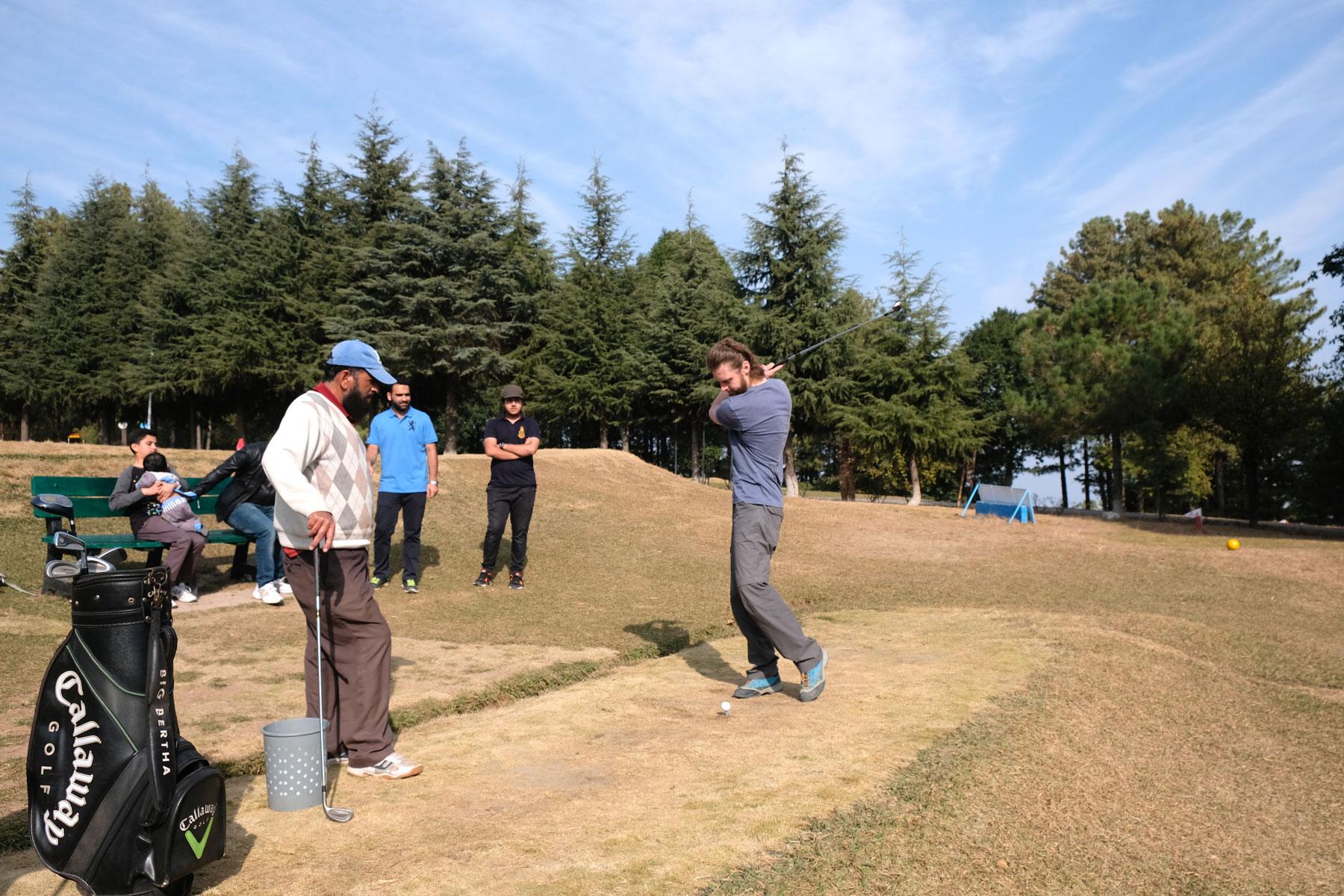 Sebastian hat Zuschauer beim Golfabschlag.