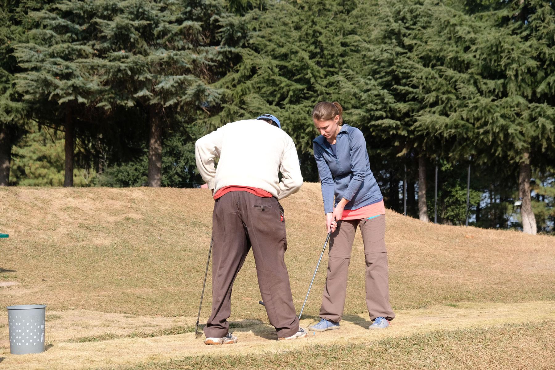 Leo übt golfen mit einem Golflehrer.