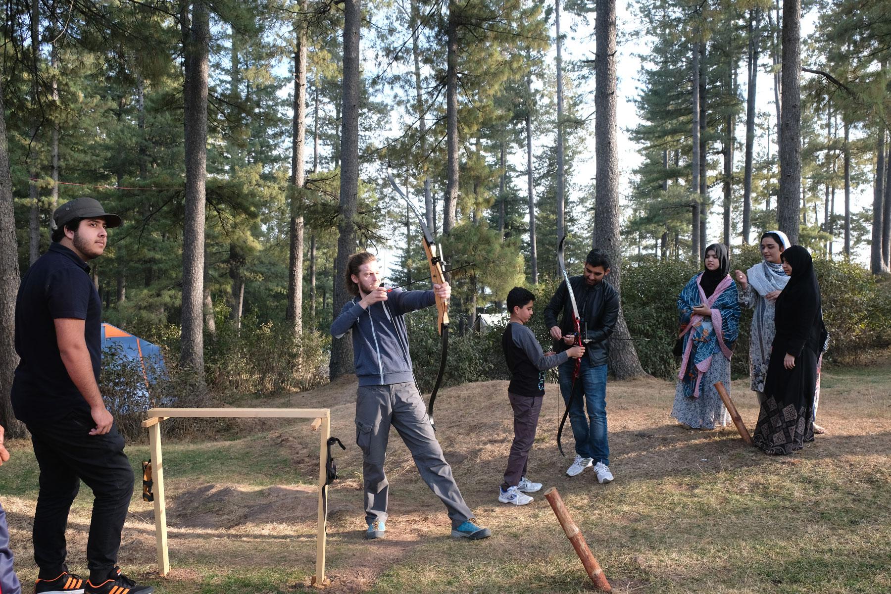 Sebastian und Pakistaner in einem Wald beim Bogenschießen.