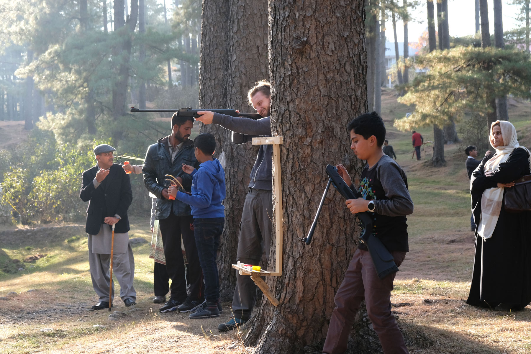 Sebastian steht zwischen zwei Bäumen und schießt mit einem Luftgewehr.