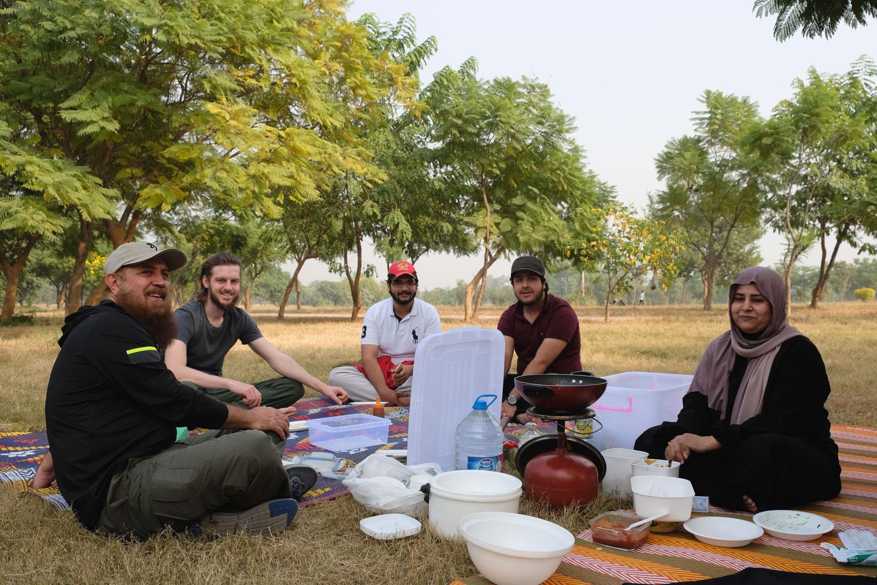 Sebastian sitzt mit einer pakistanischen Familie in einem Park beim Picknick.