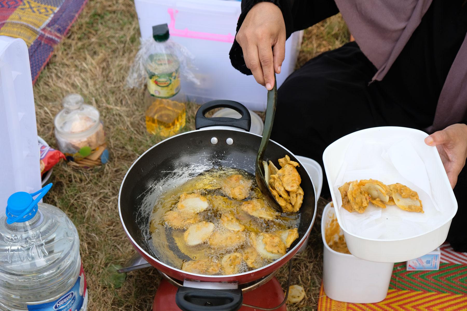 Eine Frau frittiert Pakora in einer Pfanne.