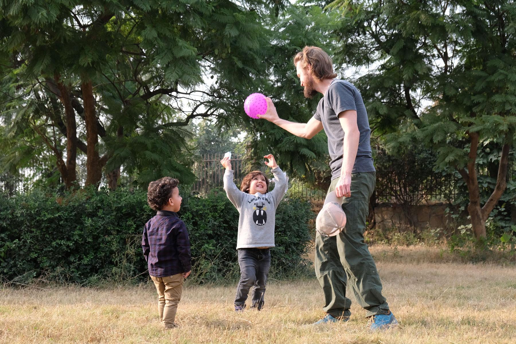 Sebastian spielt Ball mit zwei Jungen in einem Park in Islamabad.