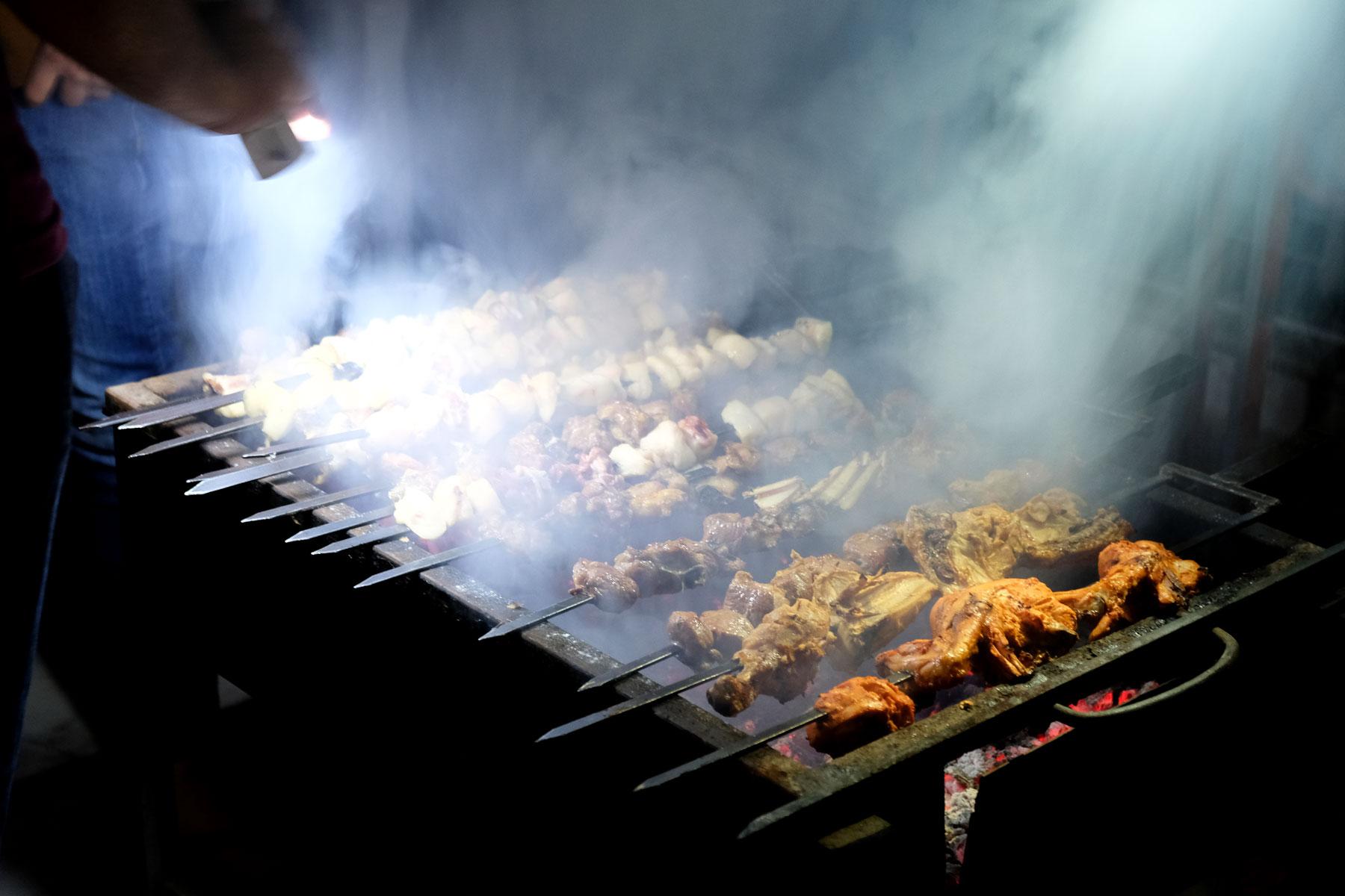 Auf einem Grill werden Fleischspieße gegrillt.