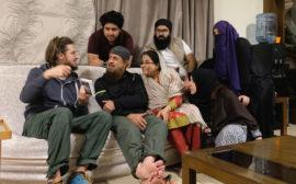 Sebastian zeigt einer pakistanischen Familie ein Fotoalbum.