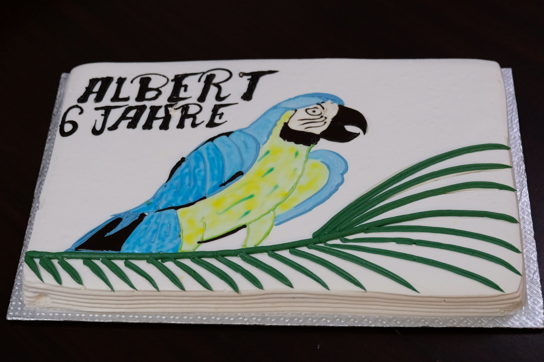"""Ein Geburtstagskuchen mit einem Papagei und der Aufschrift """"Albert 6 Jahre""""."""