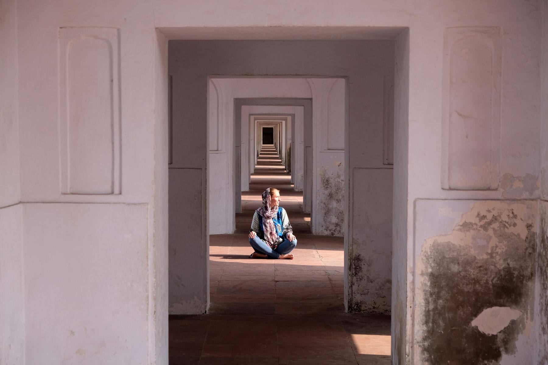 Leo sitzt in Badshahi-Moschee in einem Gang mit symmetrischen Tore.