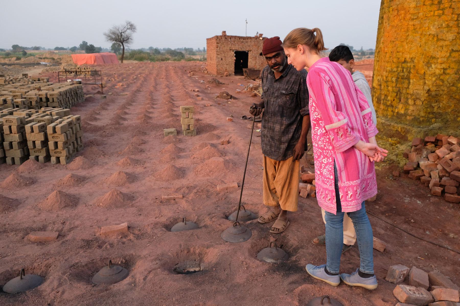 Ein pakistansicher Mann erklärt Leo, wie der Brennofen einer Ziegelbrennerei funktioniert.