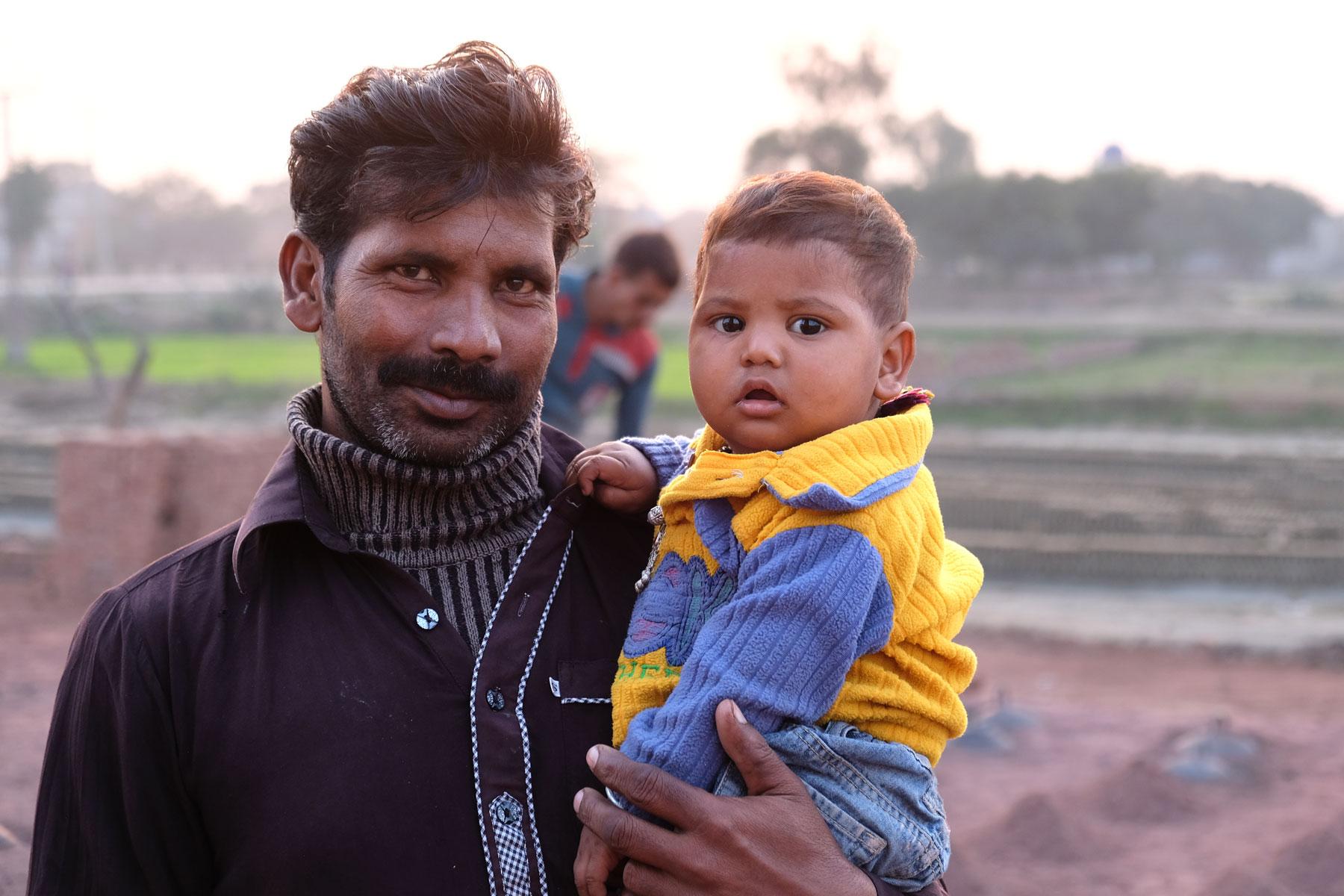 Ein pakistanischer Mann hält ein Kleinkind auf dem Arm.