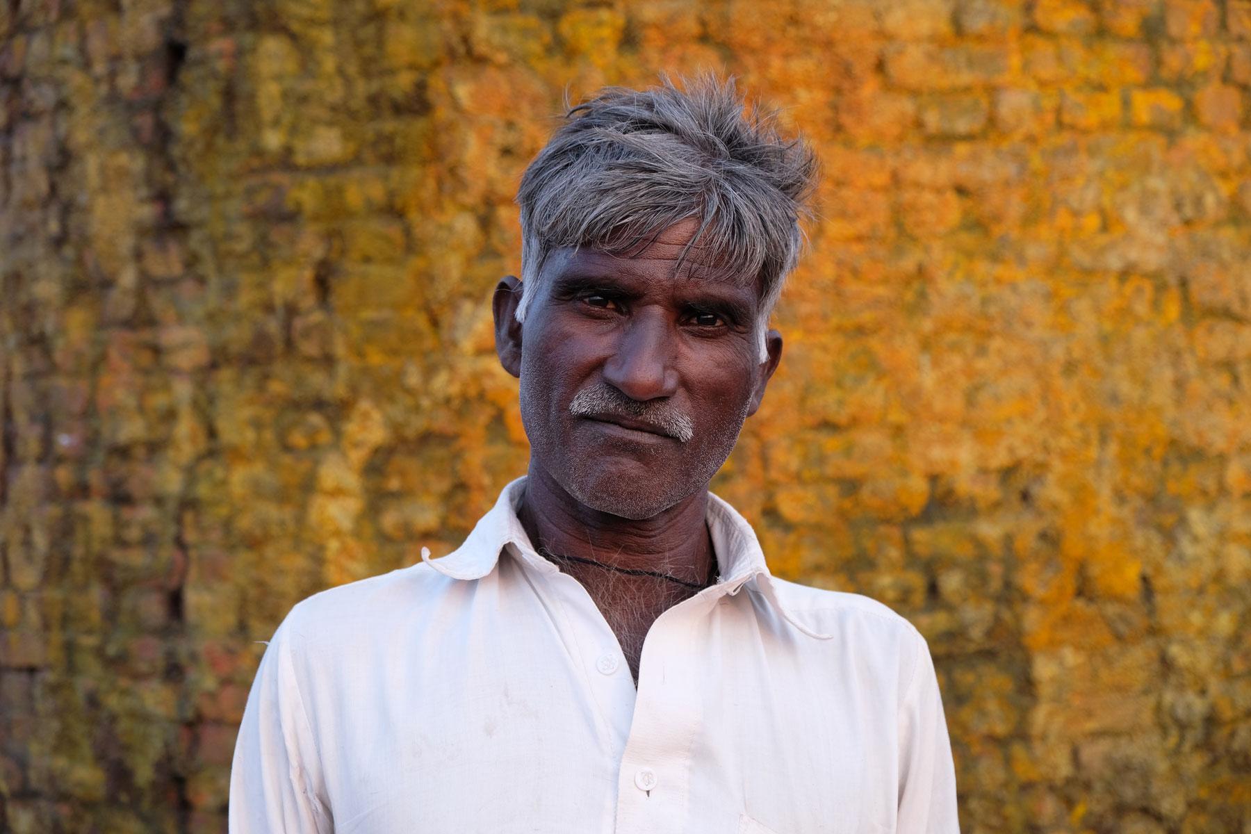 Ein Pakistaner vor dem Schornstein einer Ziegelbrennerei.