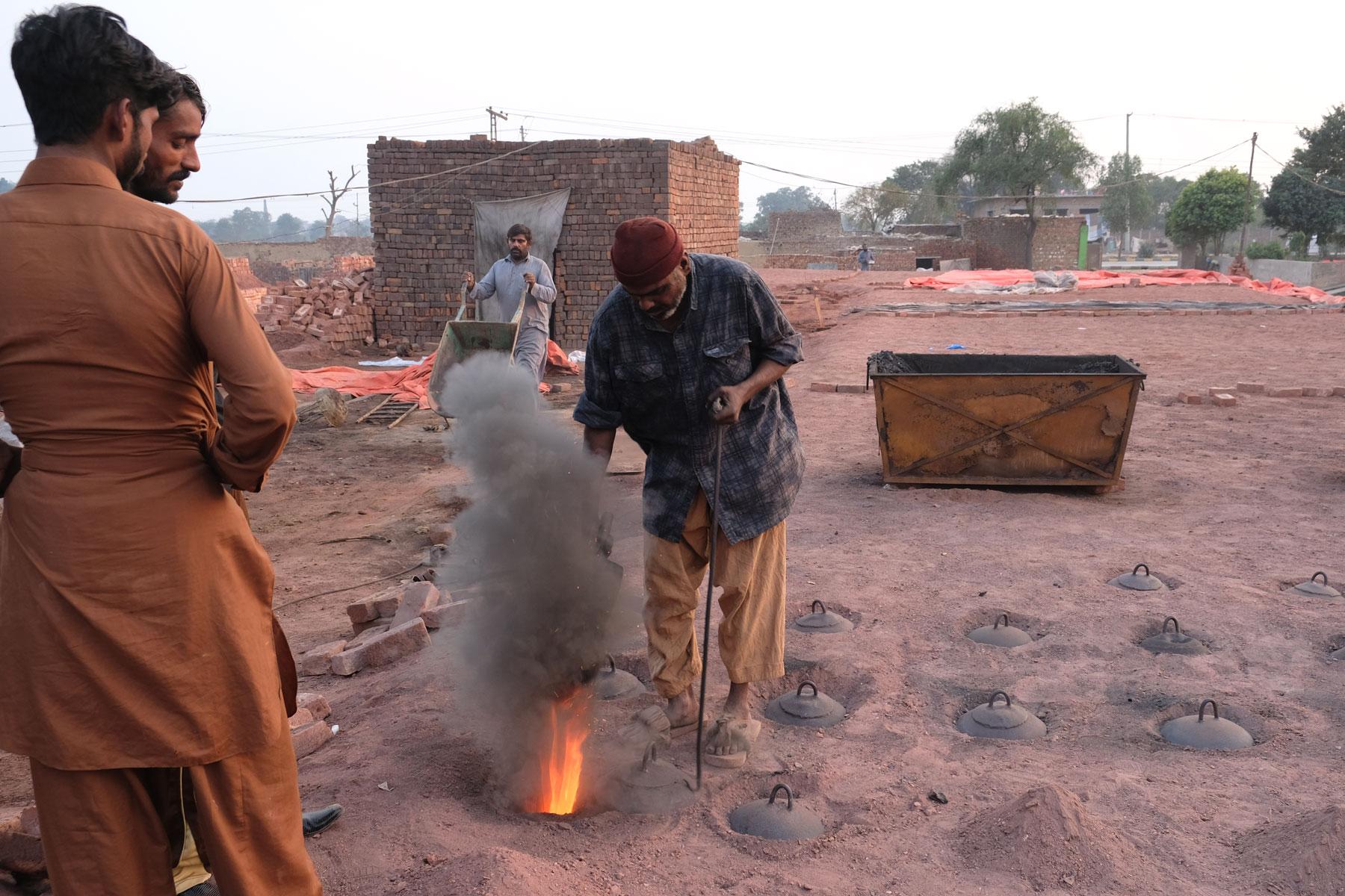Ein Arbeiter schüttet Kohle in eine Öffnung des Brennofens einer Ziegelbrennerei.