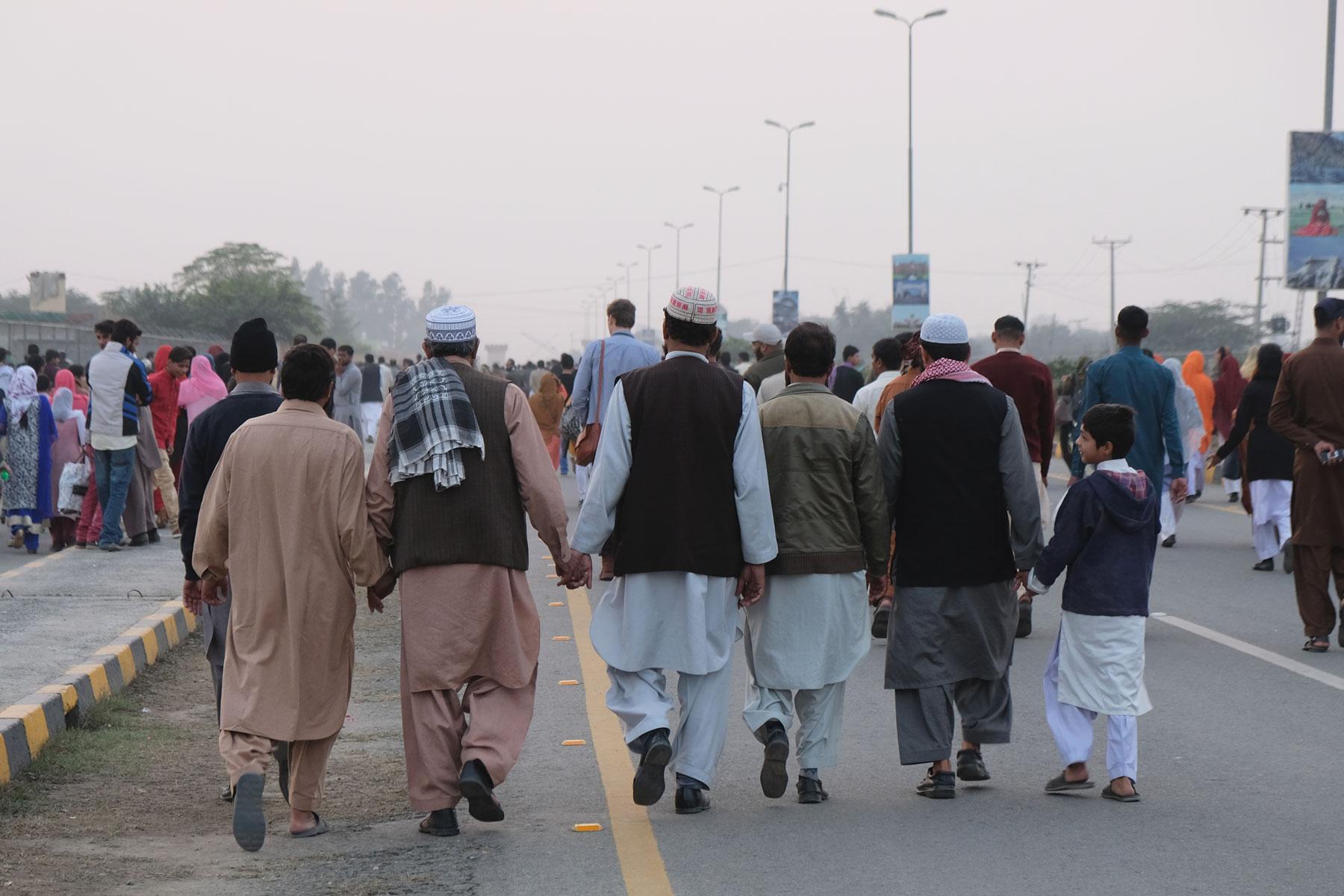 Pakistanische Soldaten gehen händchenhaltend auf einer Straße.