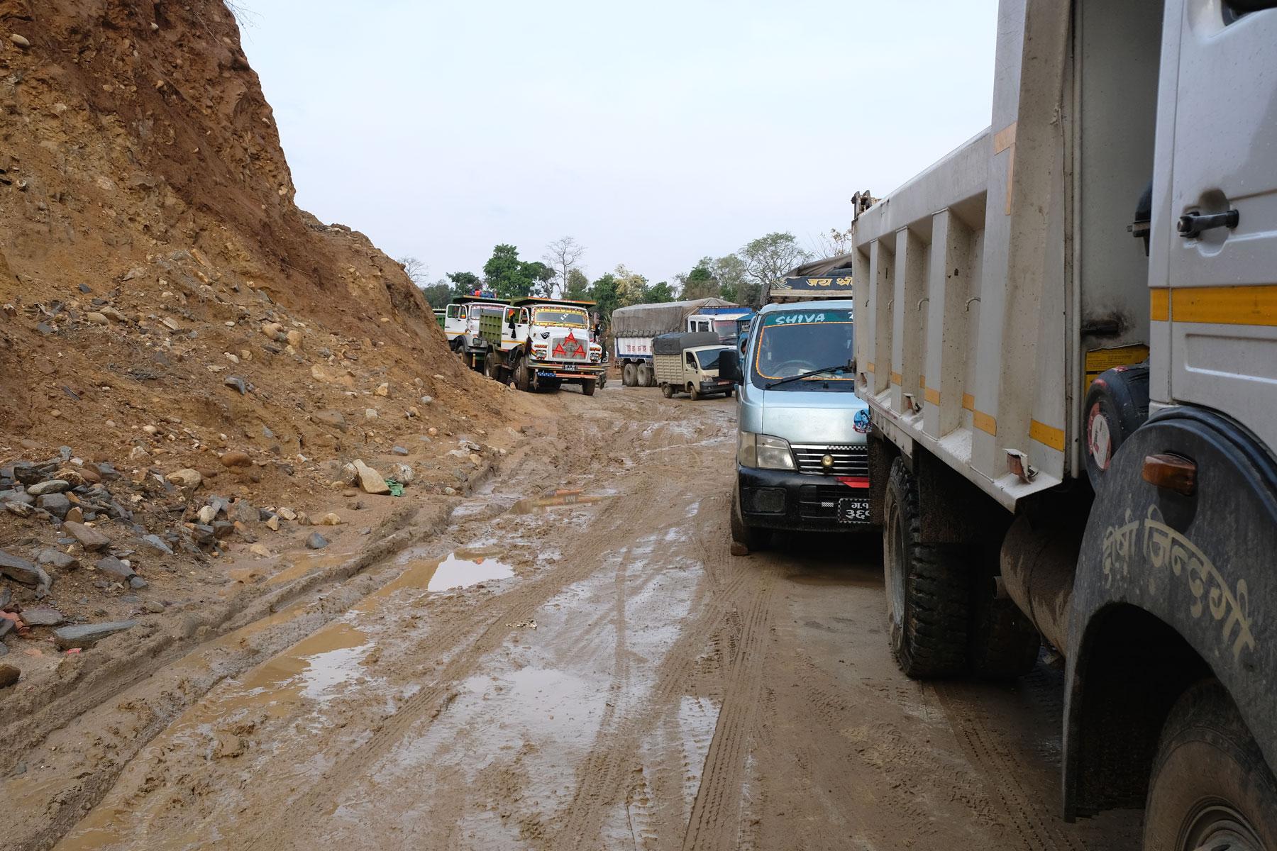 Lastwagen stehen auf einer Schlammpiste im Stau.