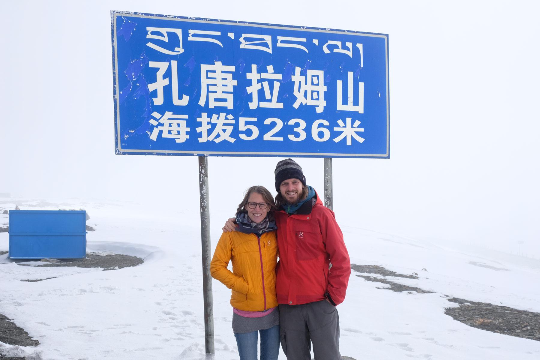 """Leo und Sebastian stehen auf dem schneebedeckten Friendship Highway vor einem Schild mit der Aufschrift """"5236""""."""