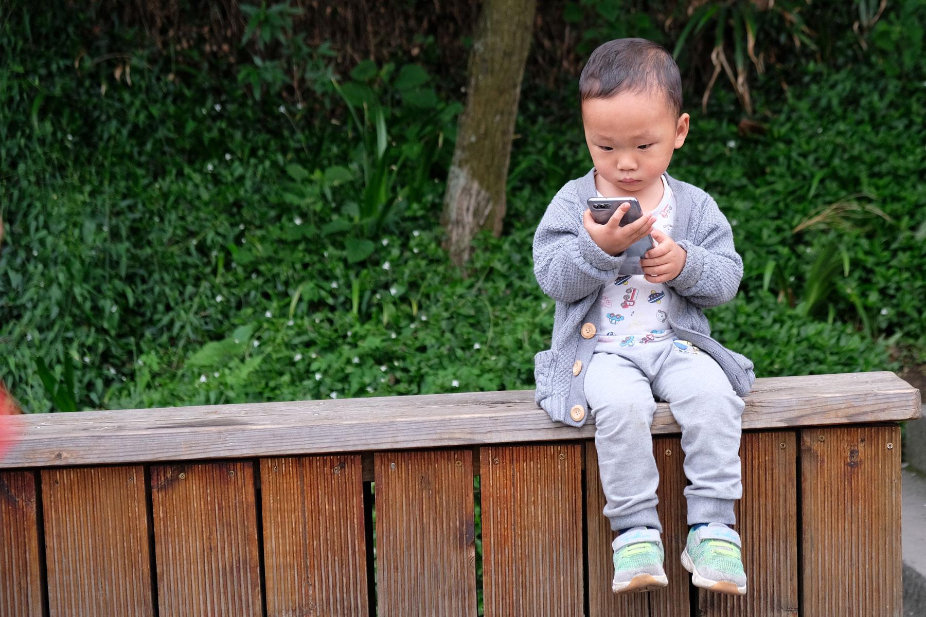 Ein chinesischer Junge sitzt auf einer Holzbank und hält ein Handy in der Hand.