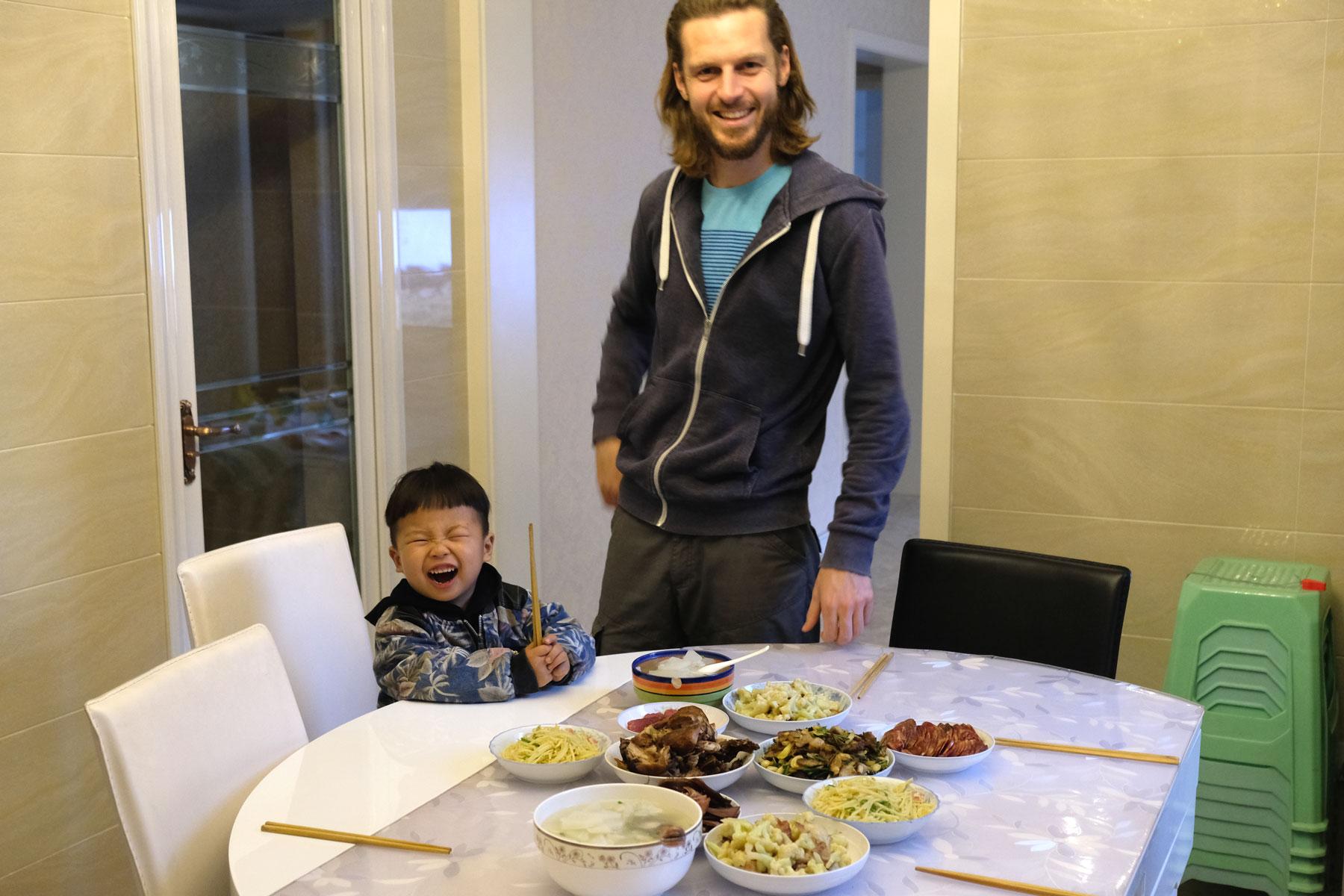 Leo steht neben einem lachenden chinesischen Jungen hinter einem gedeckten Tisch.