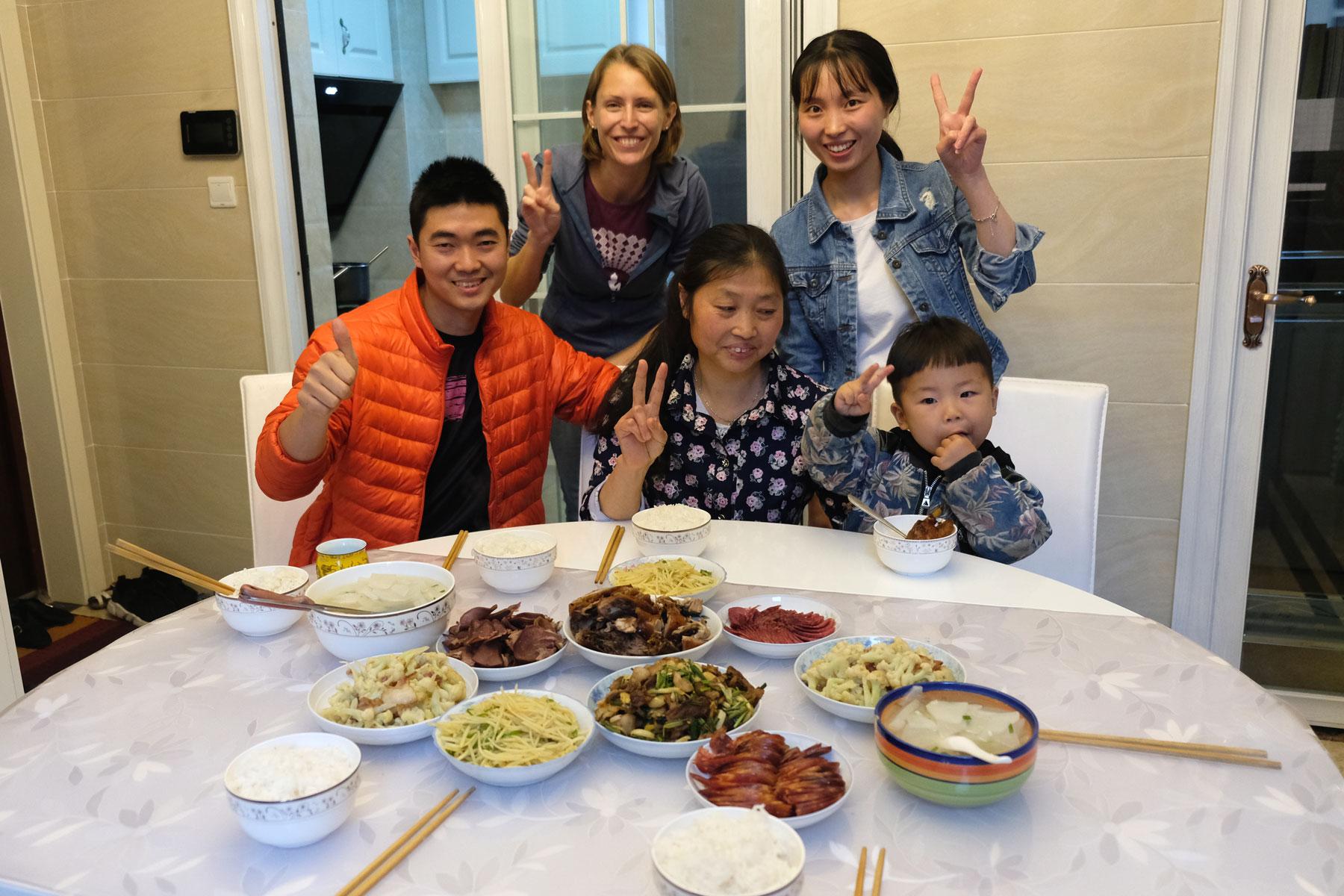 Leo mit einer chinesischen Familie vor einem gedeckten Tisch.