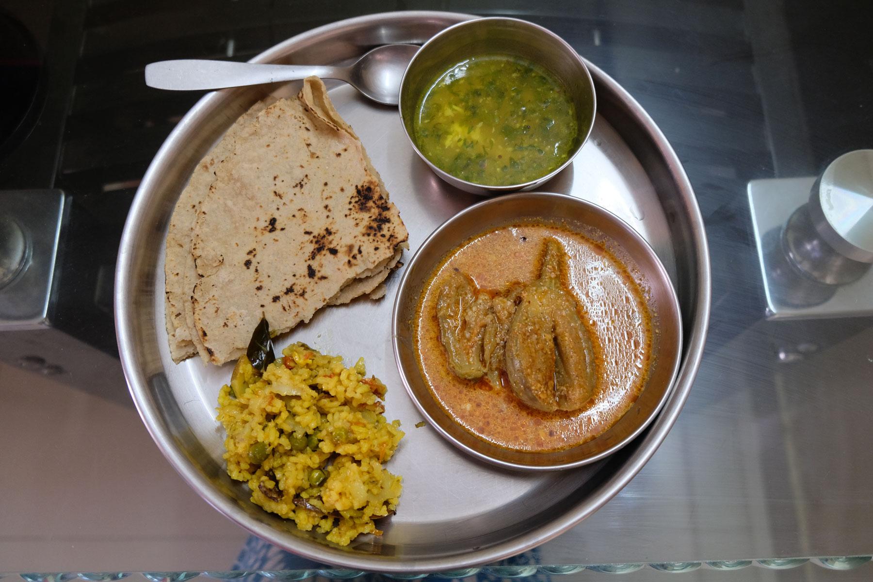 Ein Stahlteller mit Chapati, Gemüsechurry, Suppe und Reis.