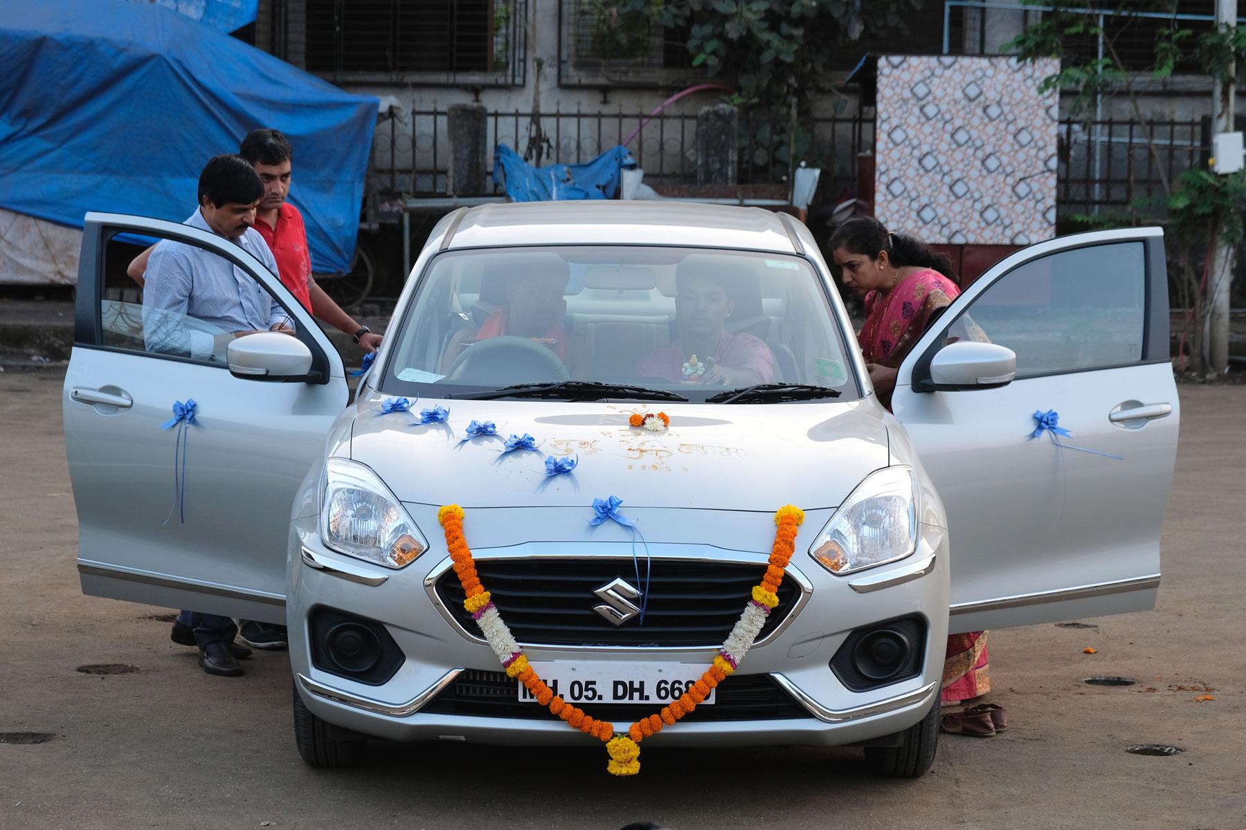 Indische Menschen schauen ein mit Blumen geschmücktes Auto an.