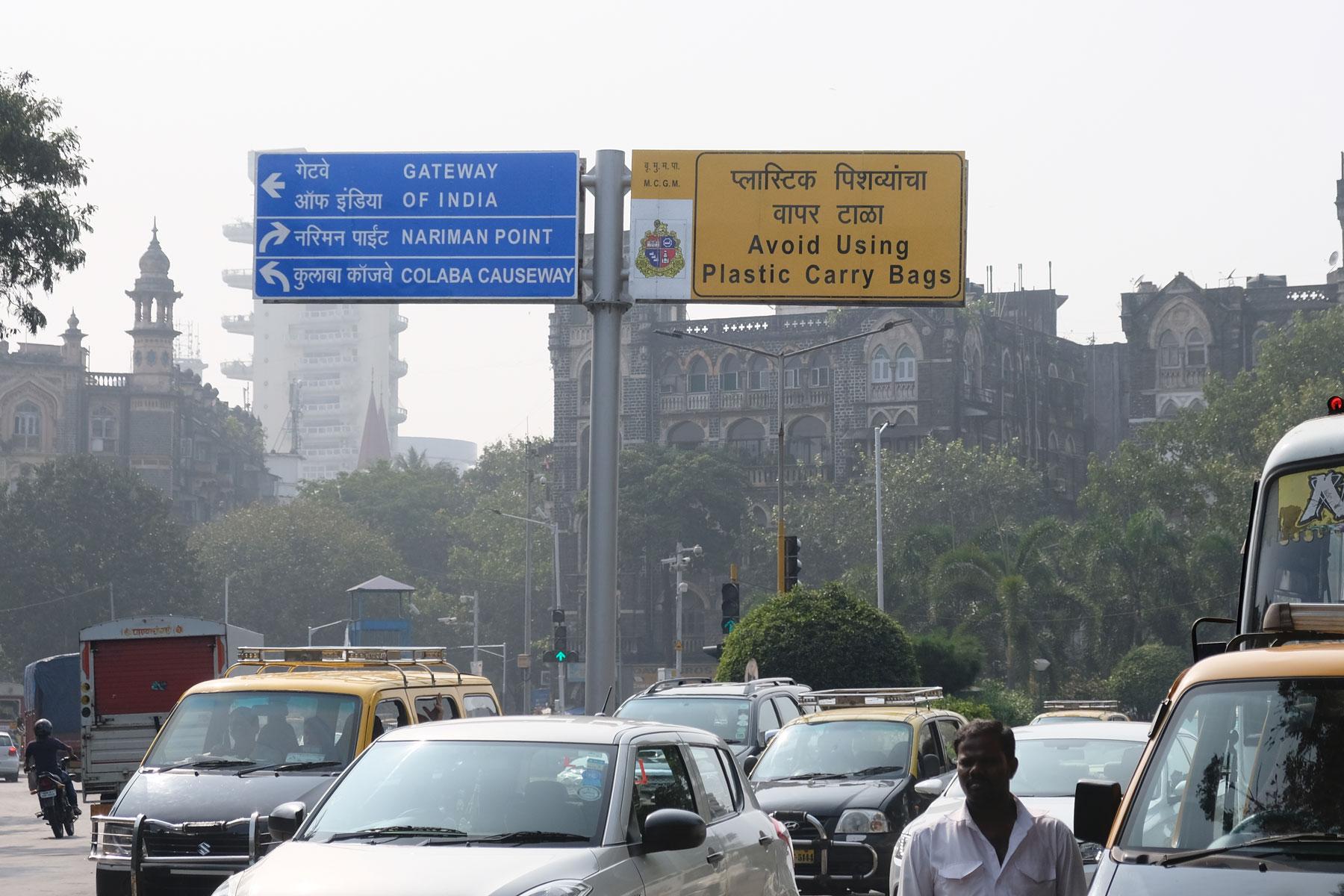 Eine Straße in Mumbai mit einem Straßenschild das darum auffordert, keine Plastiktüten zu benutzen.