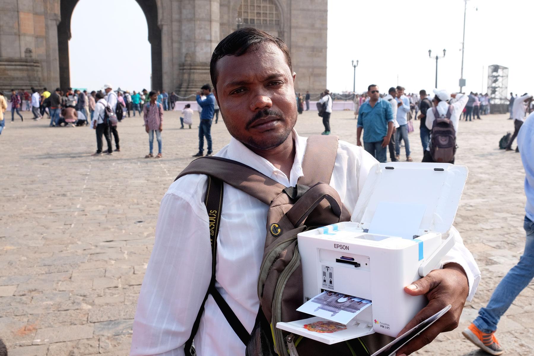 Ein indischer Mann in Mumbai mit einem tragbaren Drucker für Papierbilder.