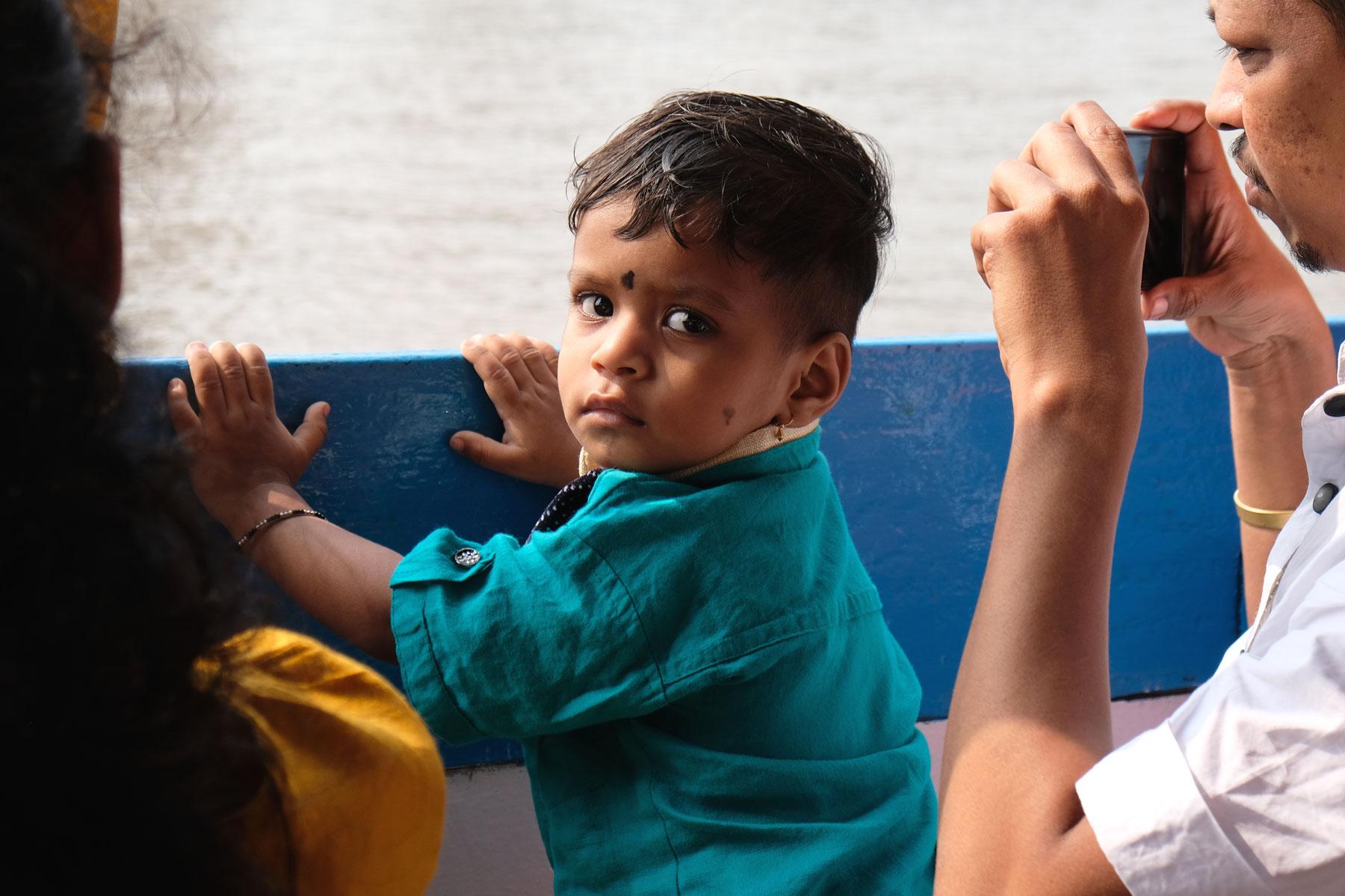 Ein indischer Mann macht auf einem Boot ein Foto von seinem Sohn.