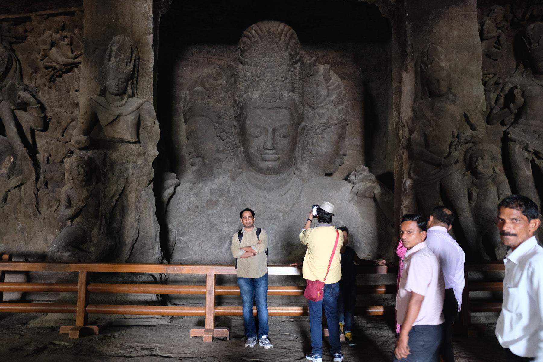 Menschen vor der Trimurti-Skulptur im Inneren der Elephanta Caves.
