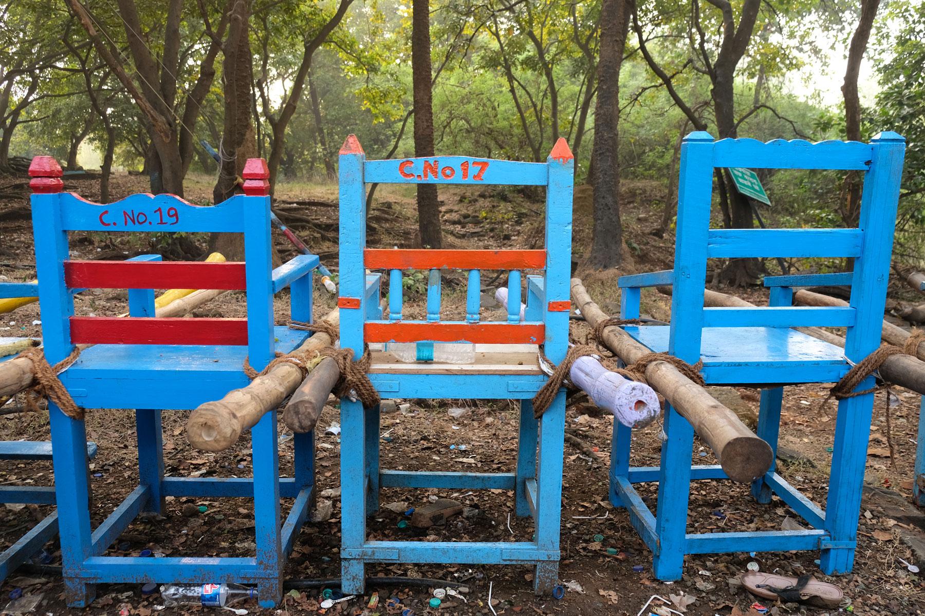 Drei Stühle, an deren Seiten lange Holzstangen befestigt sind.