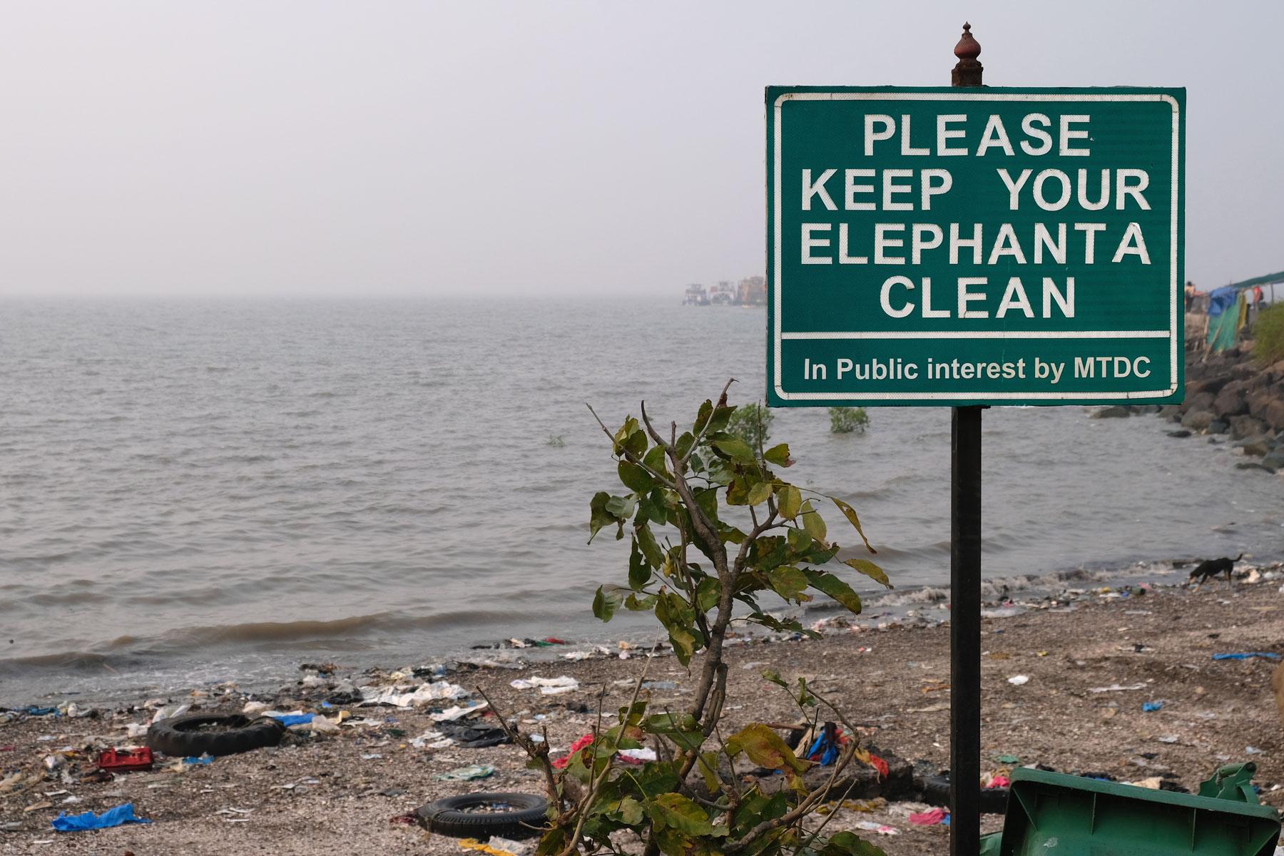 Ein schmutziger Strand auf Elephanta Island und ein Hinweisschild, das darum bittet, die Insel sauber zu halten.