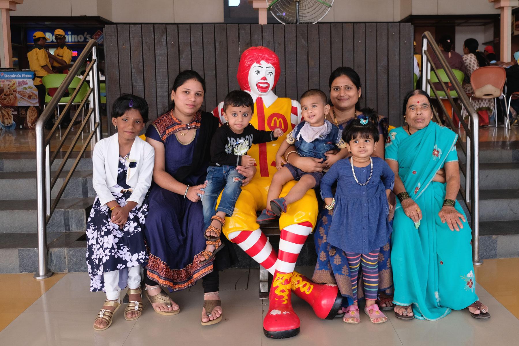 Eine indische Familie sitzt neben einer Figur von Ronald McDonald.