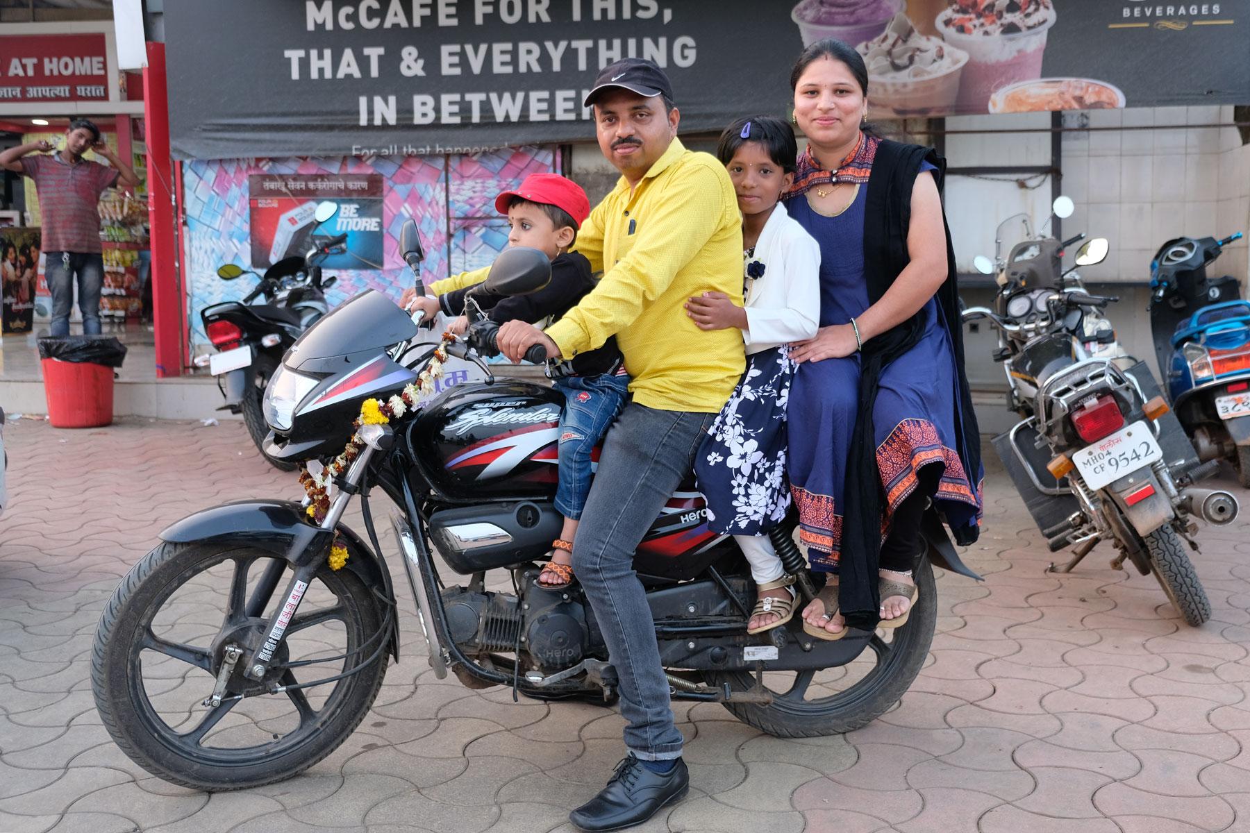 Eine indische Famlie sitzt auf einem Motorrad.