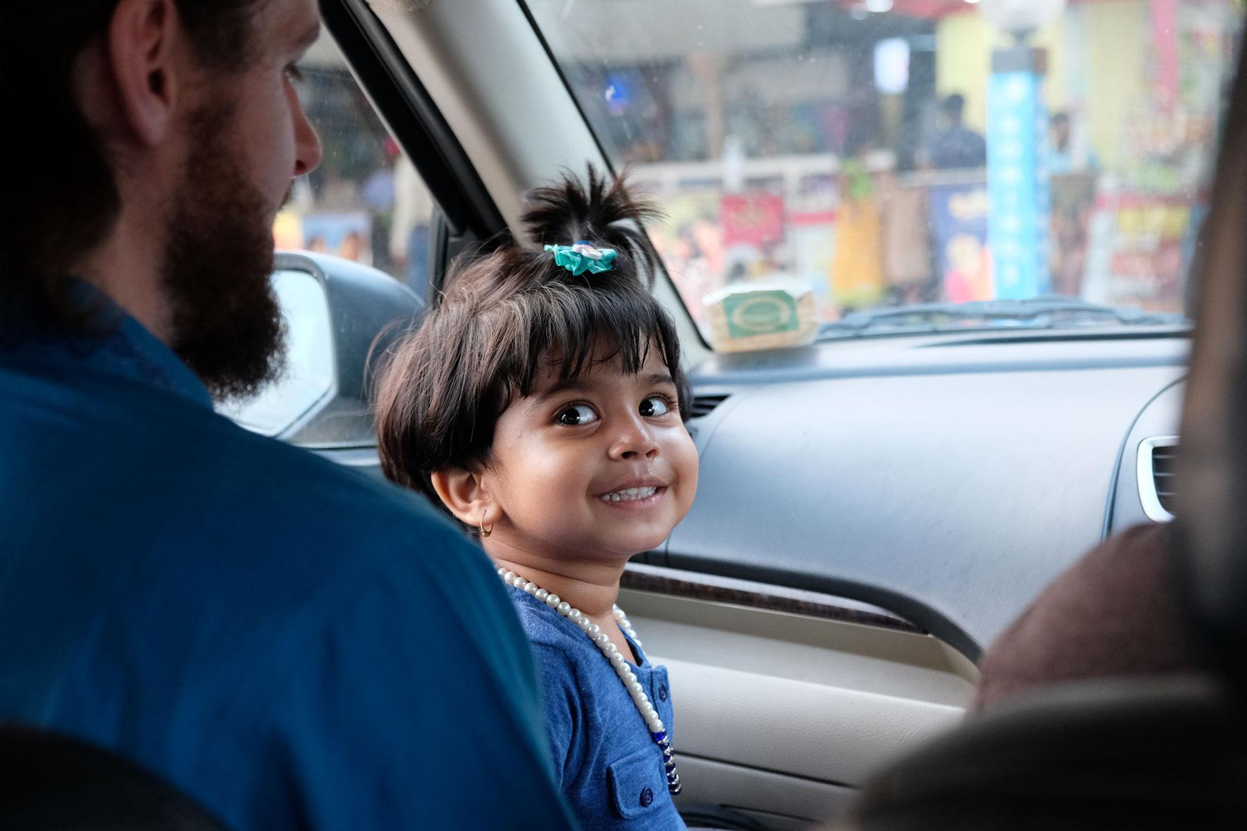 Sebastian und ein indisches Mädchen sitzen in einem Auto in Mumbai.