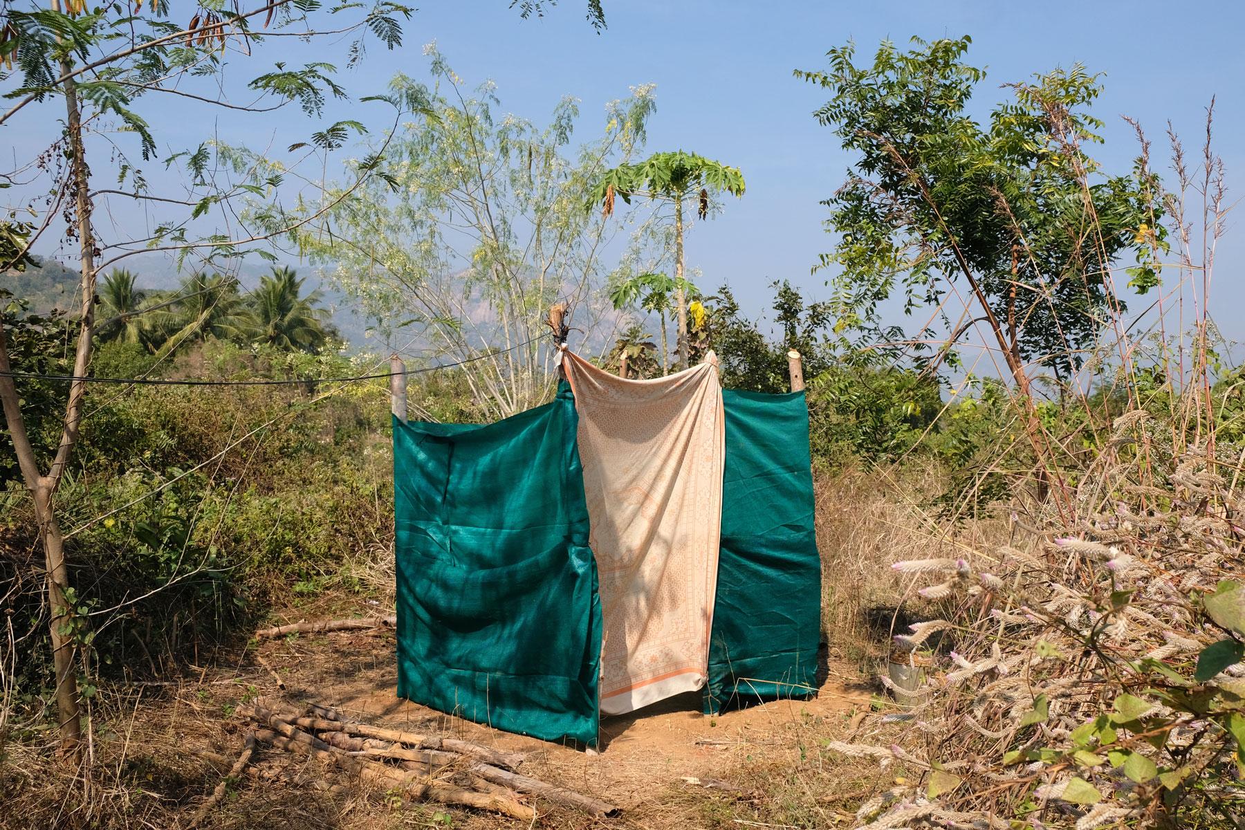 Ein mit grünnen Stoffbahnen errichtetes Toilettenhäusschen auf einer Farm.