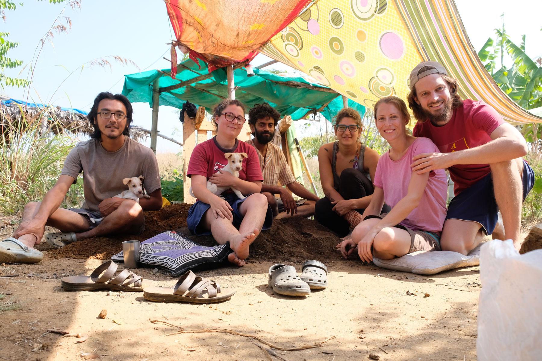 Leo und Sebastian sitzen mit Freiwilligen auf dem Boden einer Permakultur-Farm in Indien.