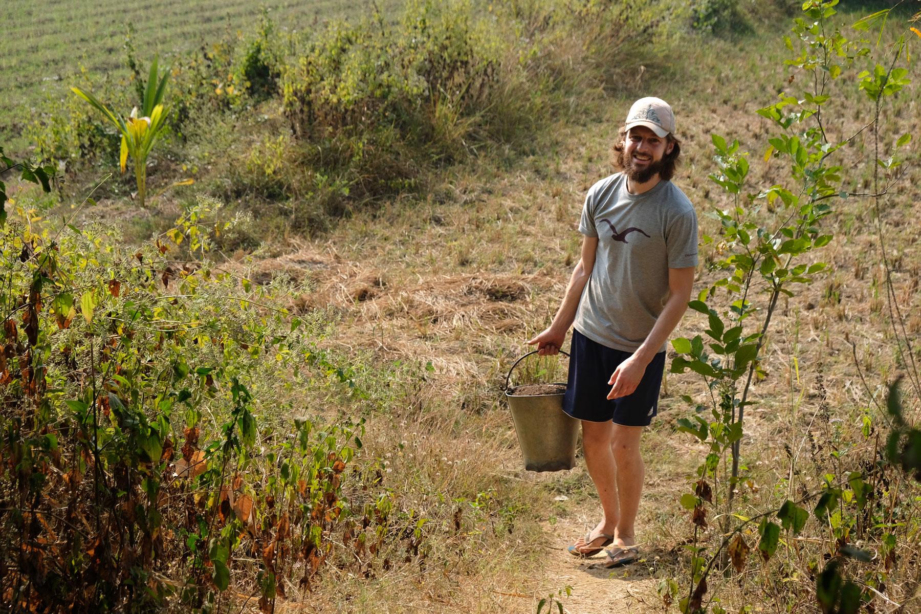 Sebastian trägt einen Eimer mit Erde auf einer indischen Farm für Permakultur.