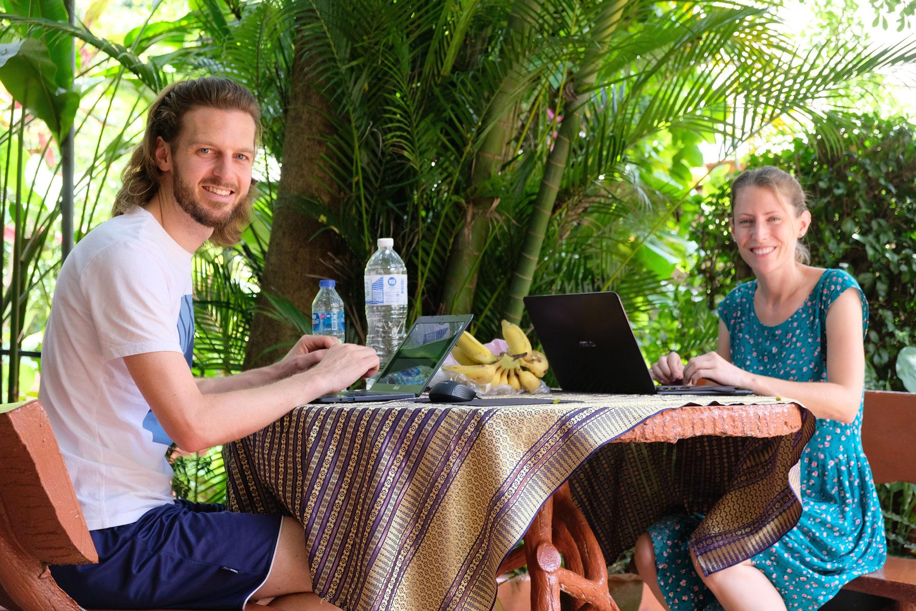 Sebastian und Leo sitzen an einem Tisch, auf dem ihre Laptops stehen.
