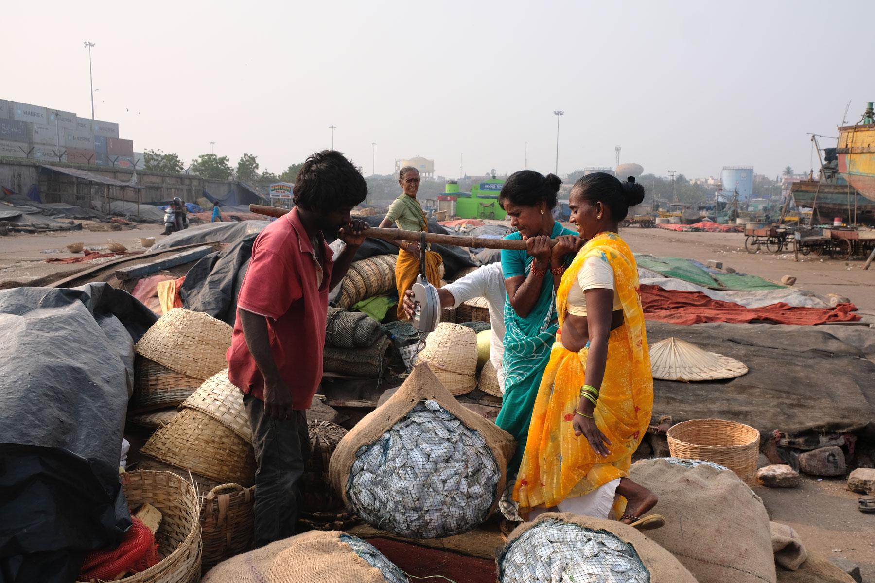 Indische Menschen wiegen am Hafen von Visakhapatnam getrockneten Fisch.