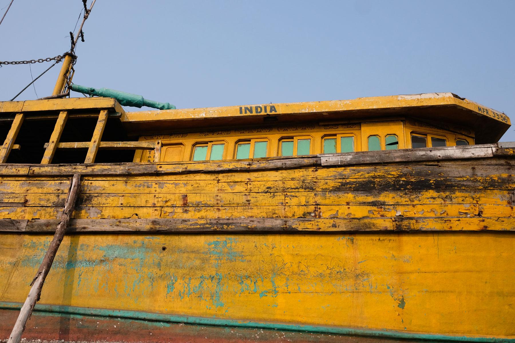 """Ein gelbes Holzschiff, auf dem das Wort """"India"""" steht."""