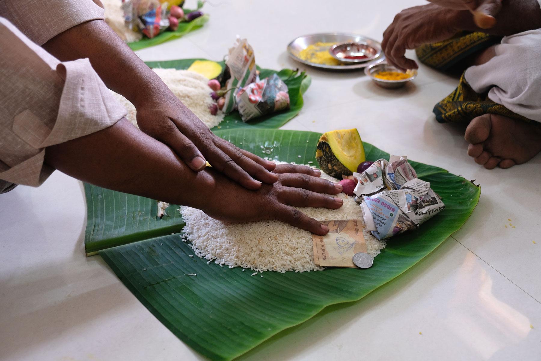 Eine Hand liegt auf ungekochtem Reis, der auf einem Bananenblatt liegt.